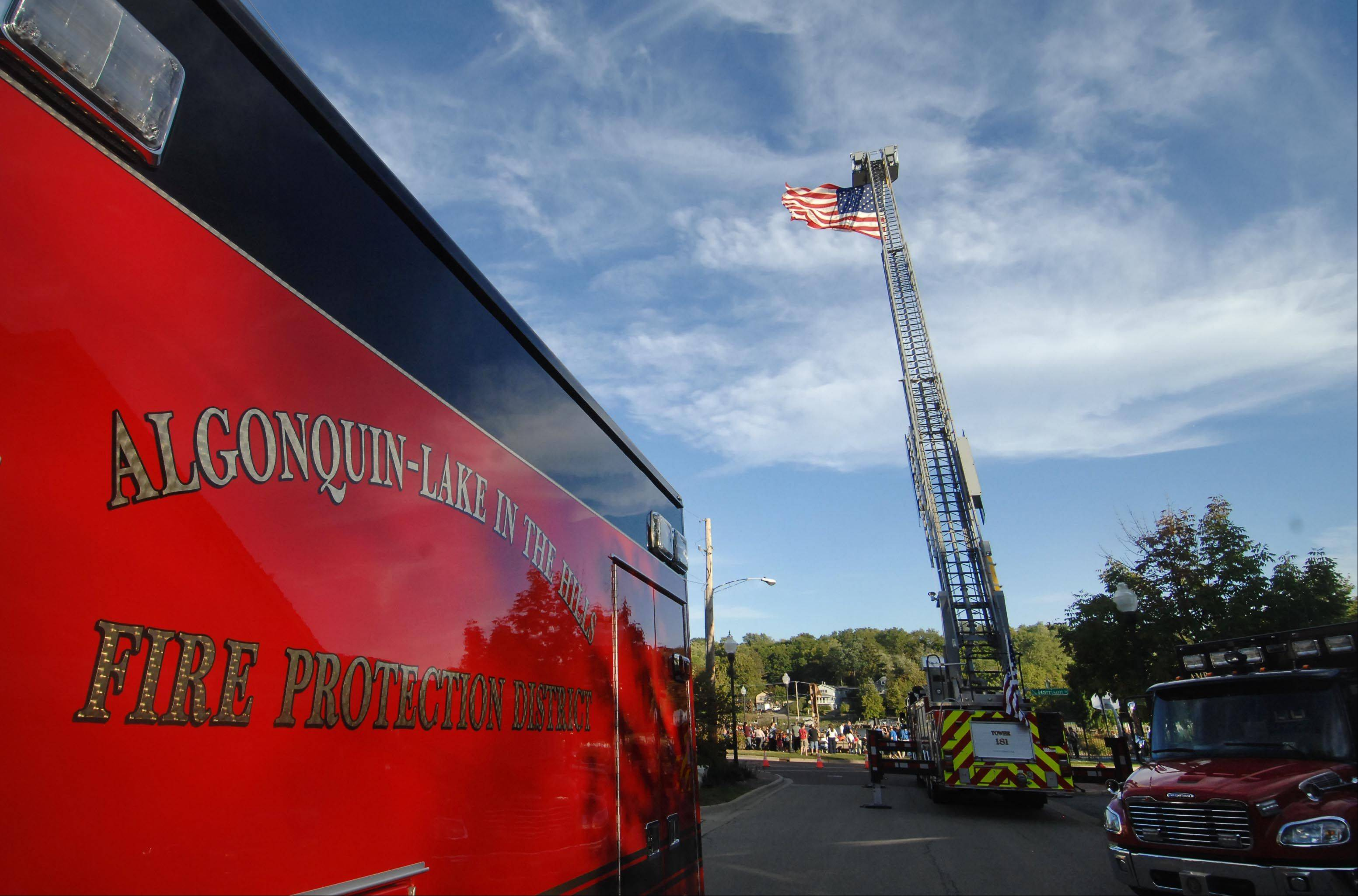 An Algonquin-Lake in the Hills Fire Protection District ladder truck displays a flag Tuesday in Algonquin during a Firefighter Memorial Dedication. The families of two firefighters killed while on duty in the last 50 years were honored also at the ceremony in Riverfront Park.