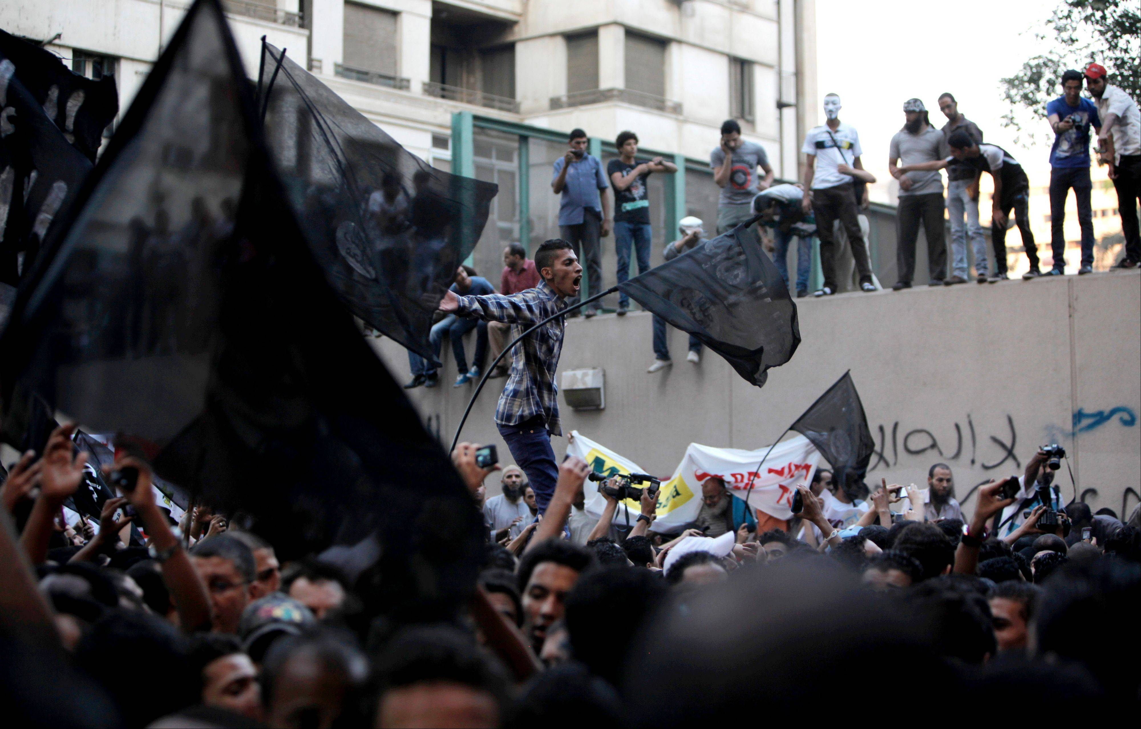 Egyptian protesters climb the walls of the U.S. embassy while others chant anti U.S. slogans during a protest in Cairo, Egypt.