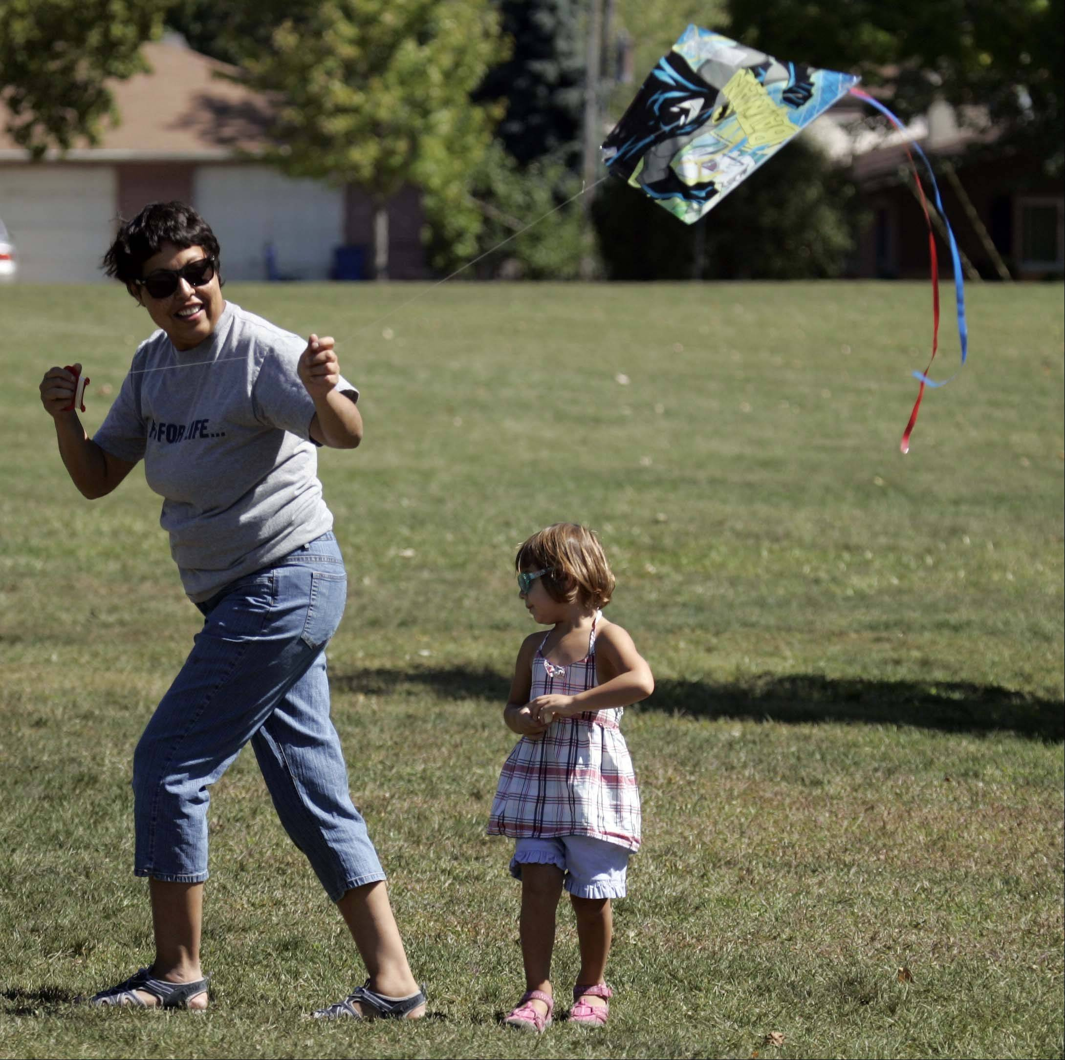 Rita Arce of West Dundee and her daughter Maya, 2, attempt to get their Batman kite to fly as they take advantage of a slightly windy but beautiful Tuesday at South End Park.