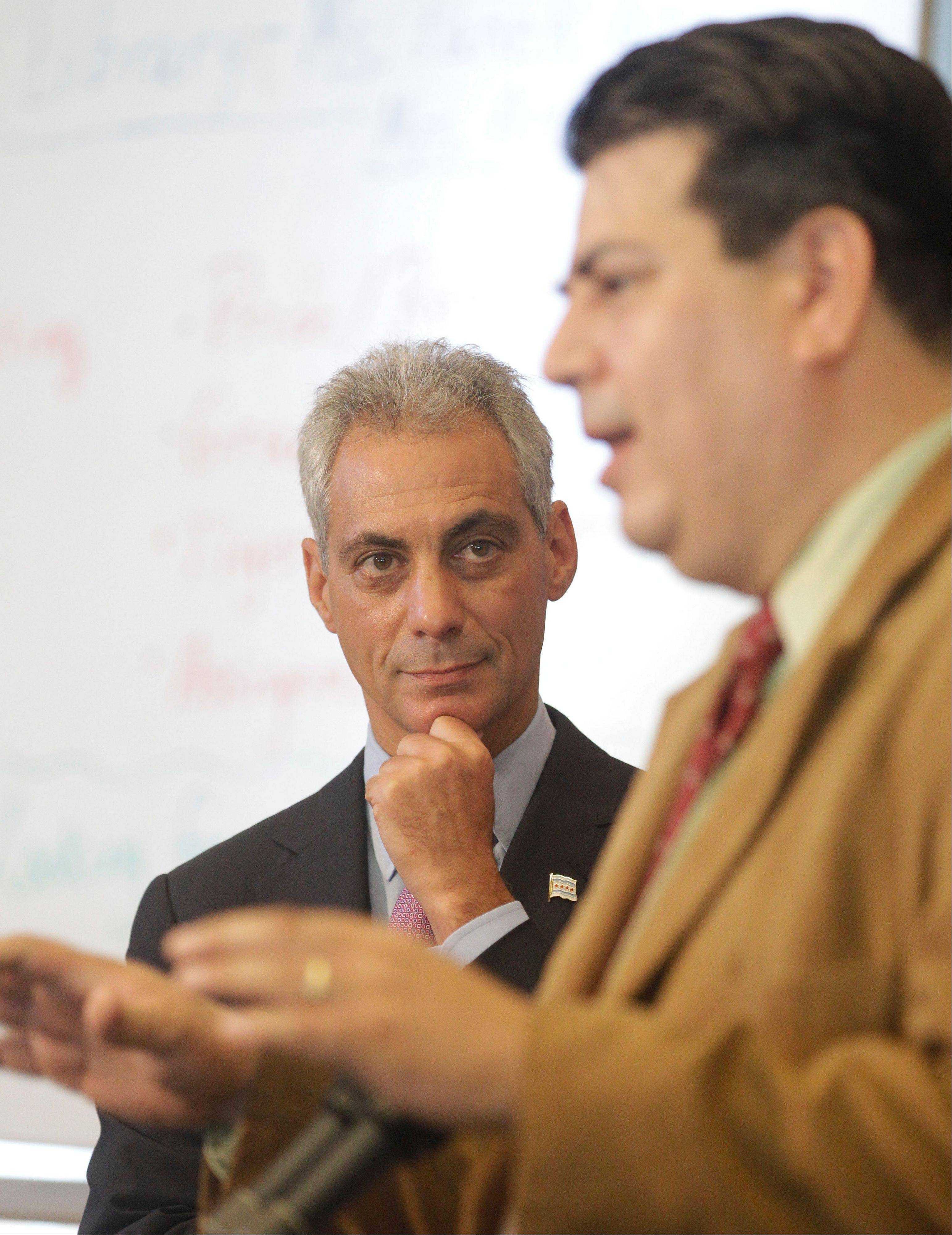 Chicago Mayor Rahm Emanuel listens during a news conference as Vincent Iturralde, principal of Tarkington School of Excellence, speaks Tuesday. Negotiations continue on the second day of a strike in the nation's third-largest school district.