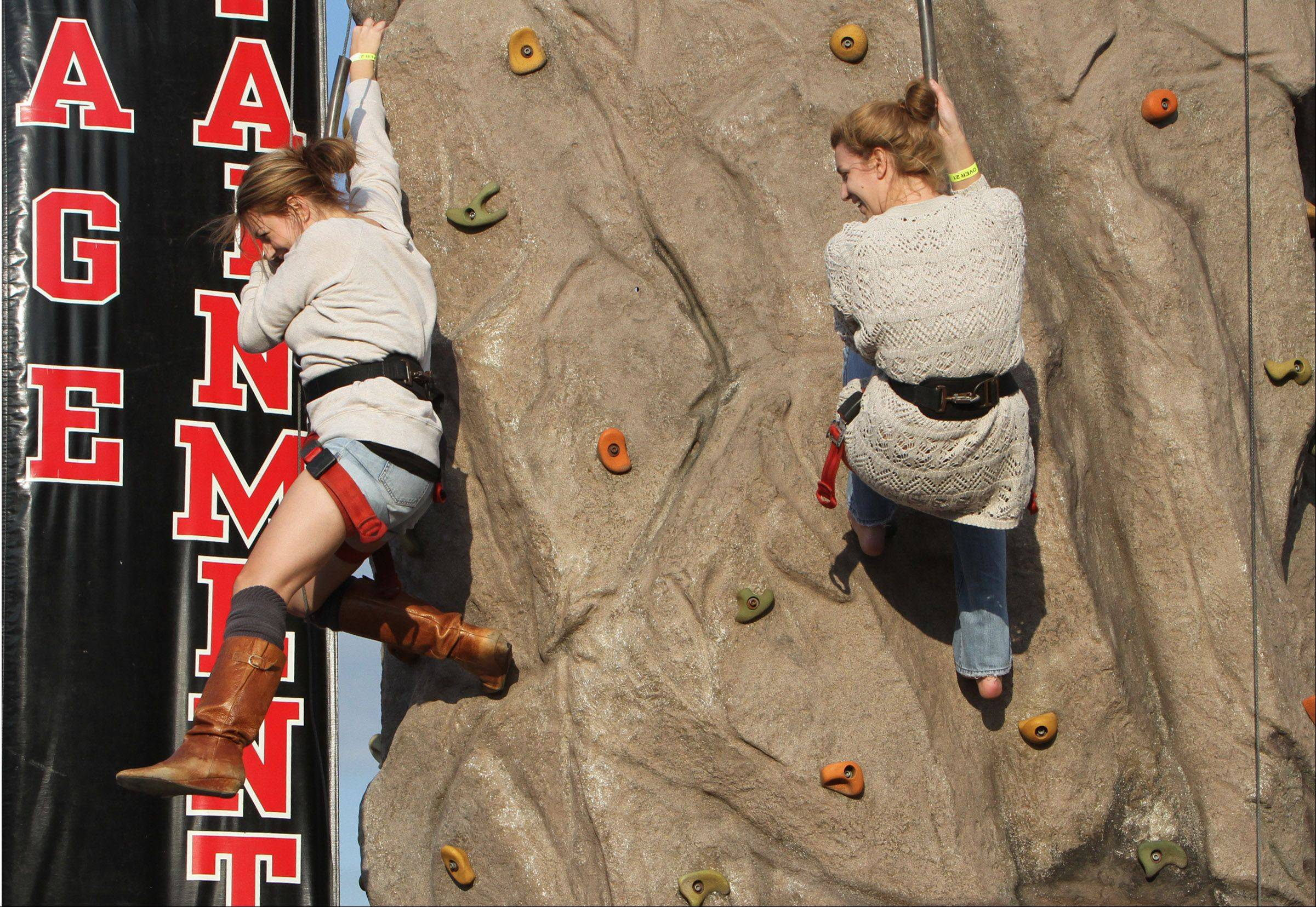 Sisters Nicki and Ellie Fisher, both of West Dundee, compete with each other to make it to the top of the climbing all at West Dundee Heritage Fest last year.