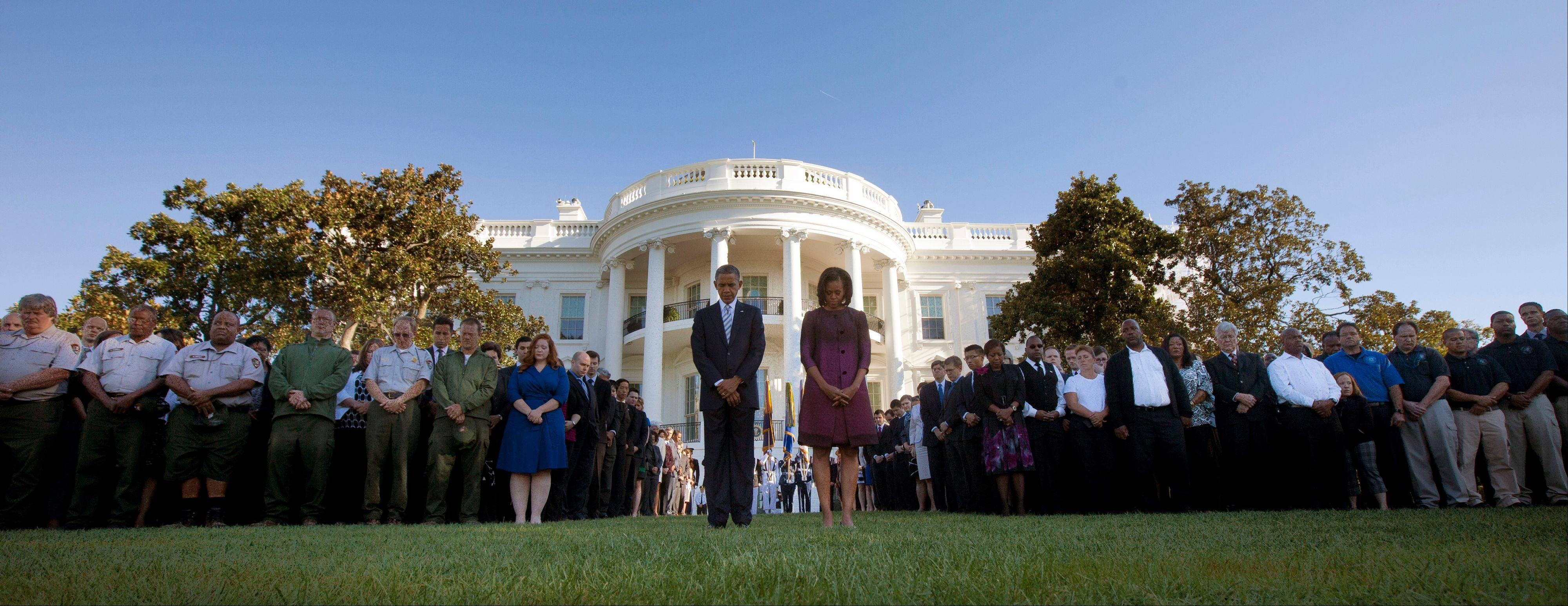 President Barack Obama and first lady Michelle Obama join members of the White House staff during a moment of silence to mark the 11th anniversary of the Sept, 11th, Tuesday, Sept. 11, 2012, on the South Lawn of the White House in Washington.