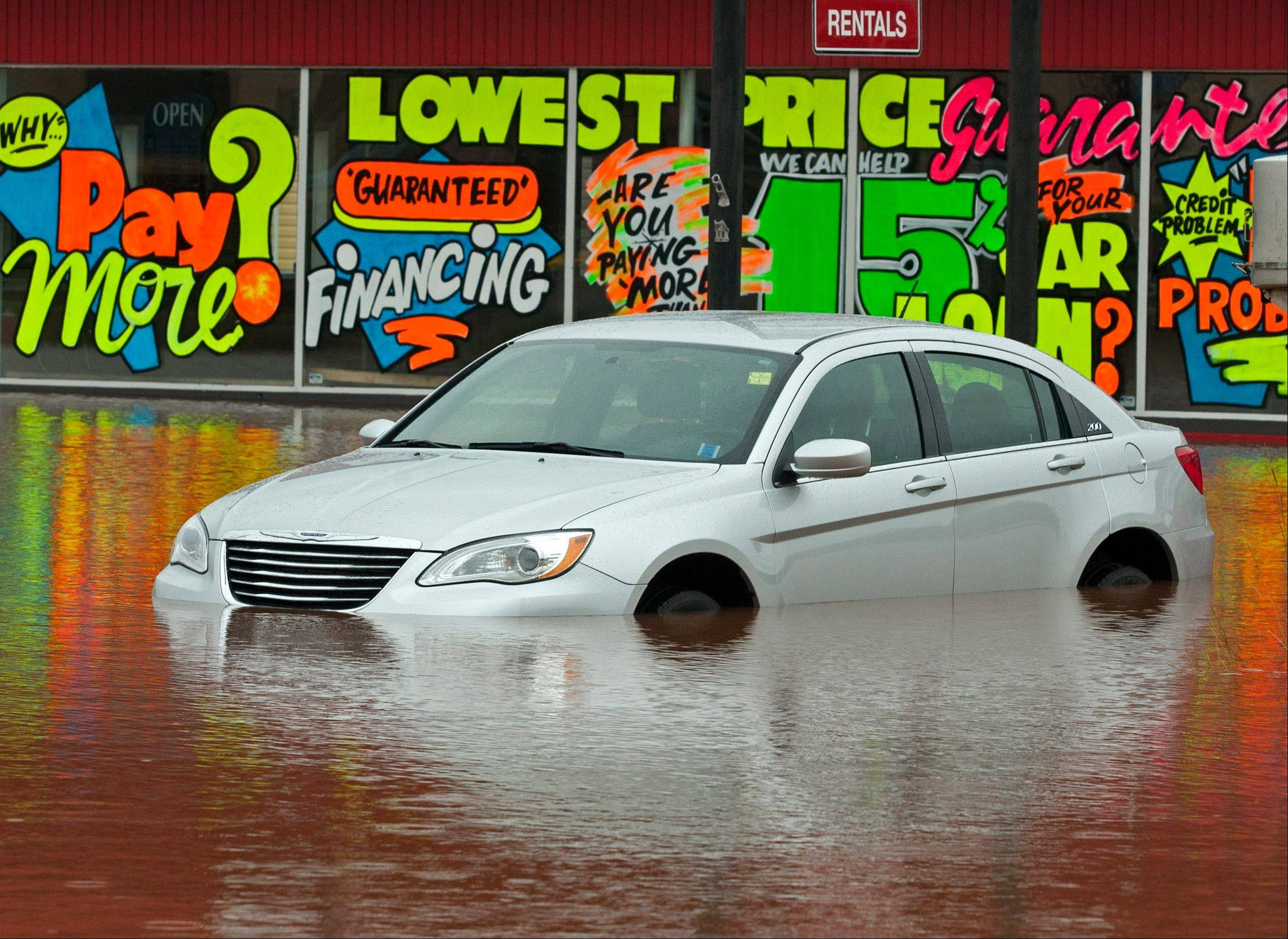 A vehicle sits outside a flooded car dealership lot after dikes on the Salmon River gave way in Truro, Nova Scotia on Monday, Sept. 10, 2012. The area is under a rainfall warning as Tropical Storm Leslie churns toward Atlantic Canada.