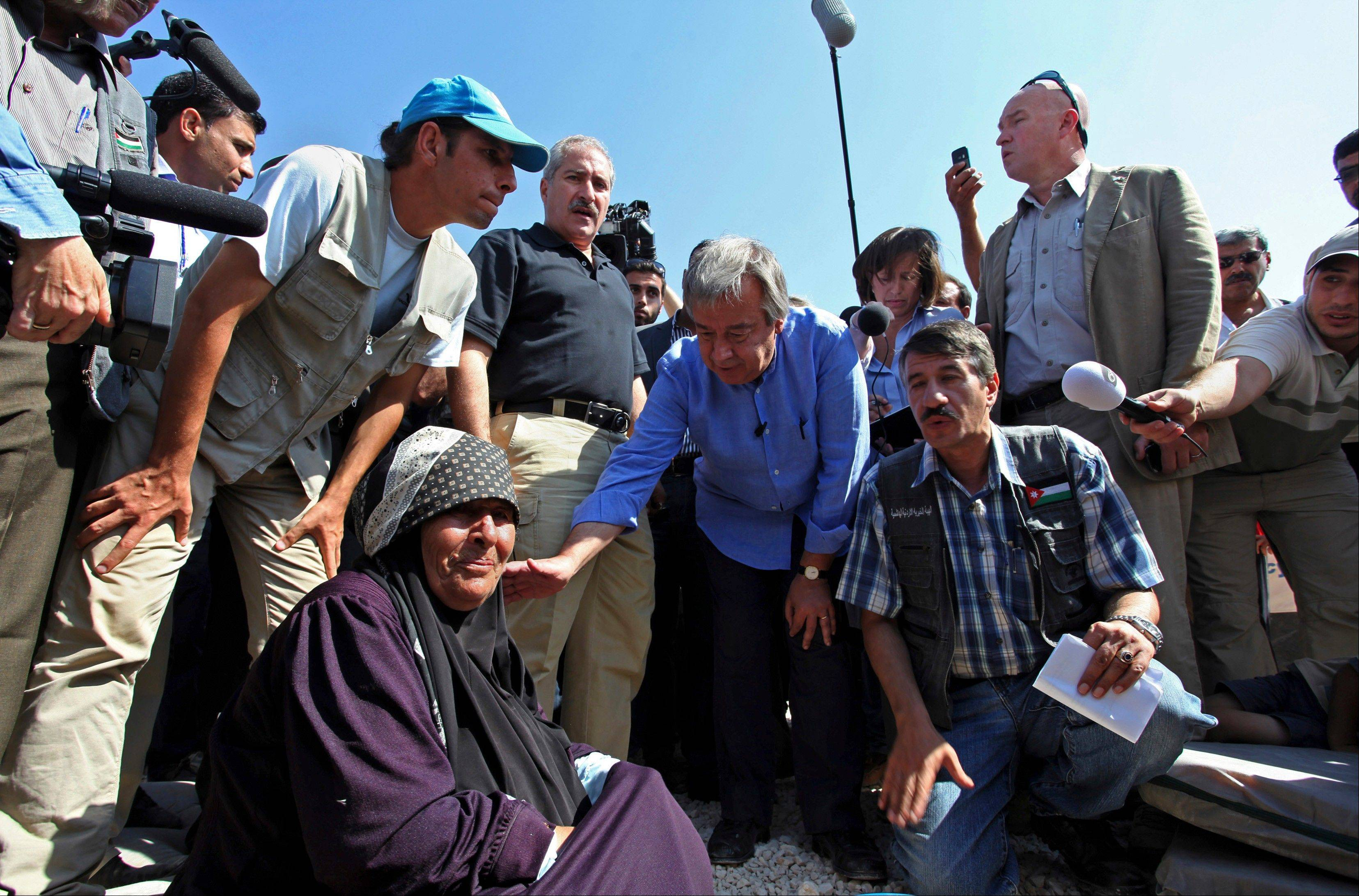 U.N. refugee chief Antonio Guterres, center, taps on the shoulder of an elderly Syrian refugee at the Zaatari Refugee Camp in Jordan for Syrians who fled the civil war in their country, Tuesday, Sept. 11, 2012. The Zaatari camp hosts about 27,000 Syrians displaced by the 18-month conflict that has so far claimed at least 23,000 lives, according to activists.