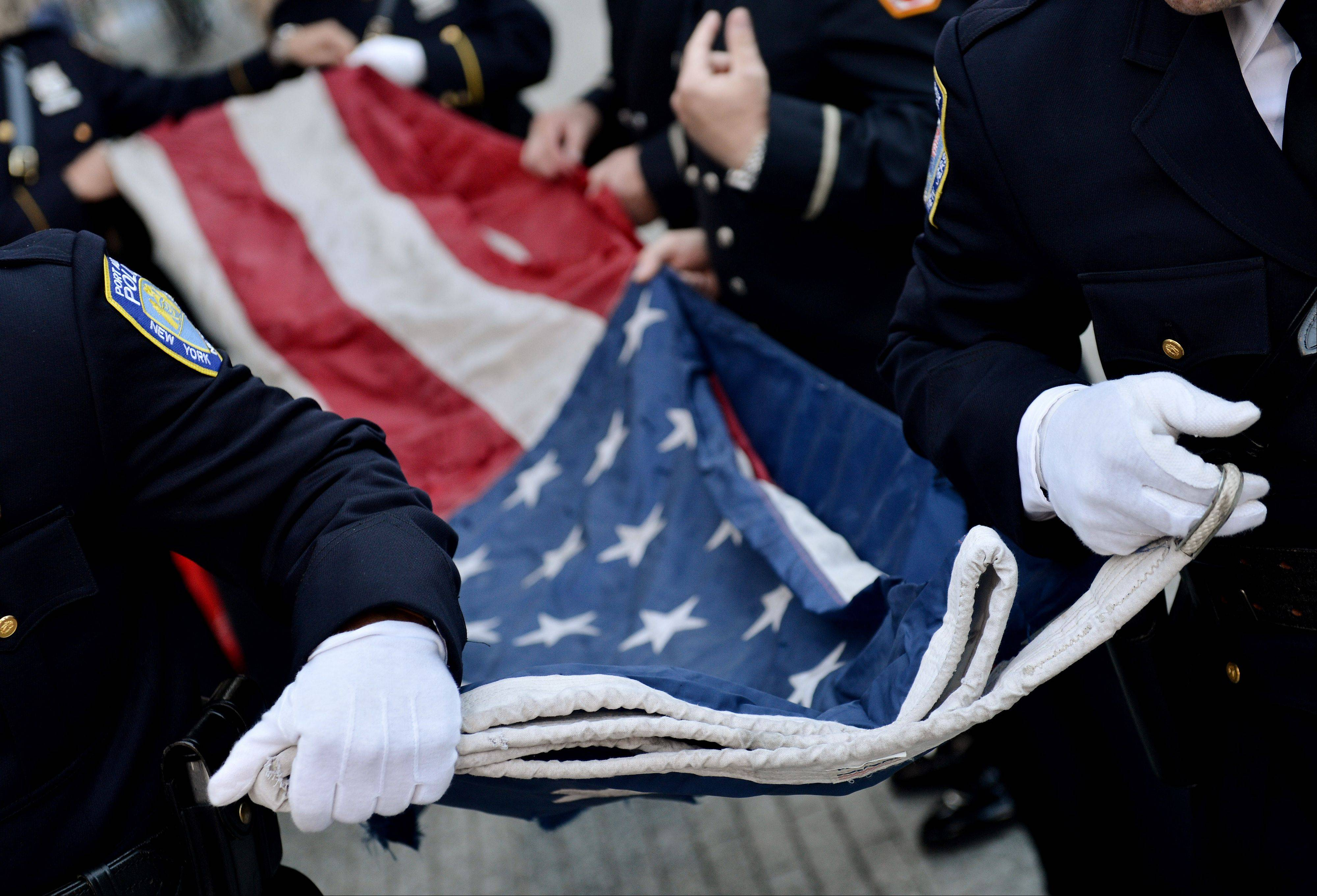 Police Officers of the Port Authority of New York and New Jersey carry an American flag that flew over at the World Trade Center towers during a ceremony marking the 11th anniversary of the attacks on the World Trade Center in New York, Tuesday, Sept. 11, 2012.