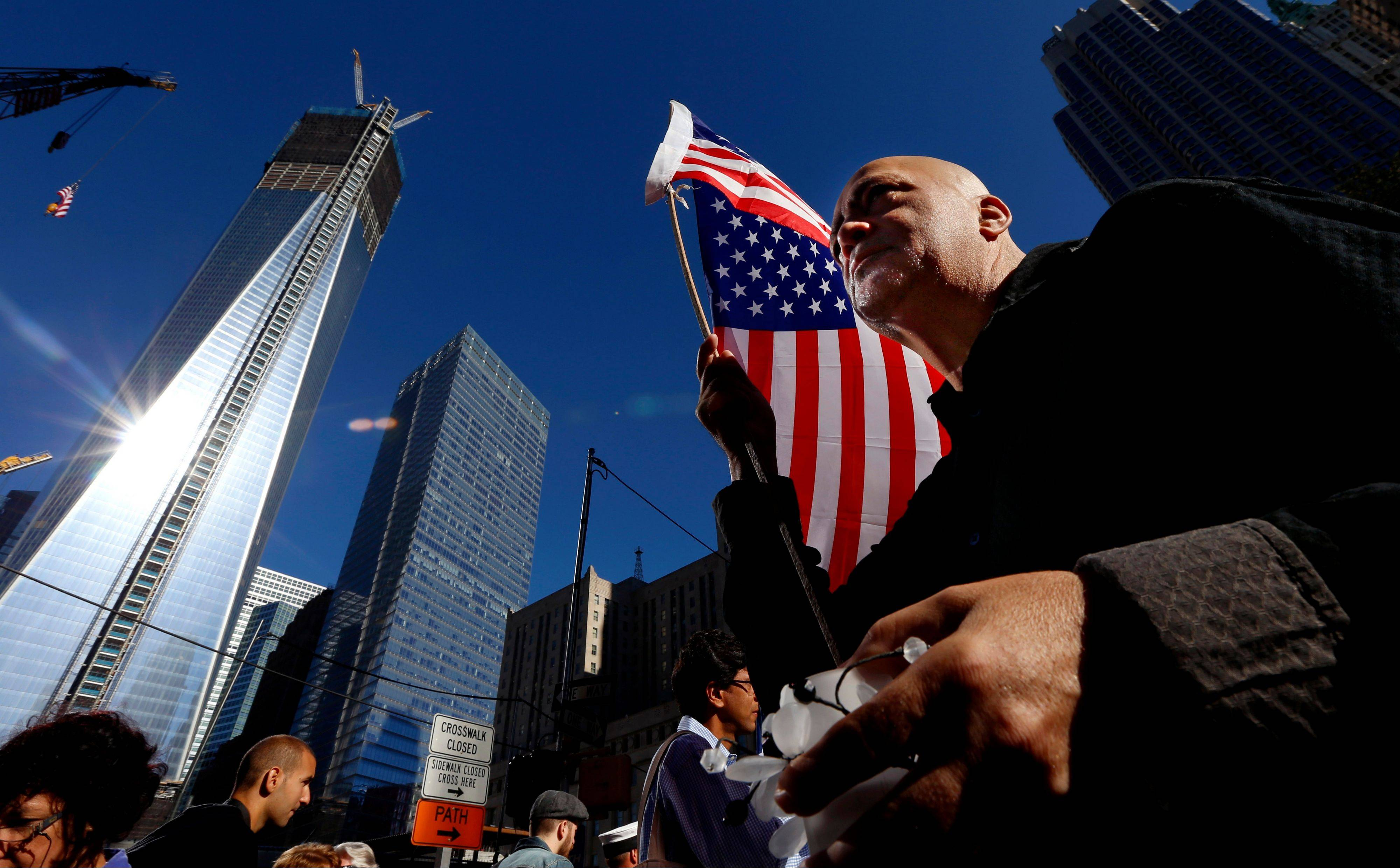 Marcio Rodriguez holds a United States flag as he pays respects in front of the construction site of One World Trade Center during the 11th anniversary of the Sept. 11 terrorist attacks in New York.