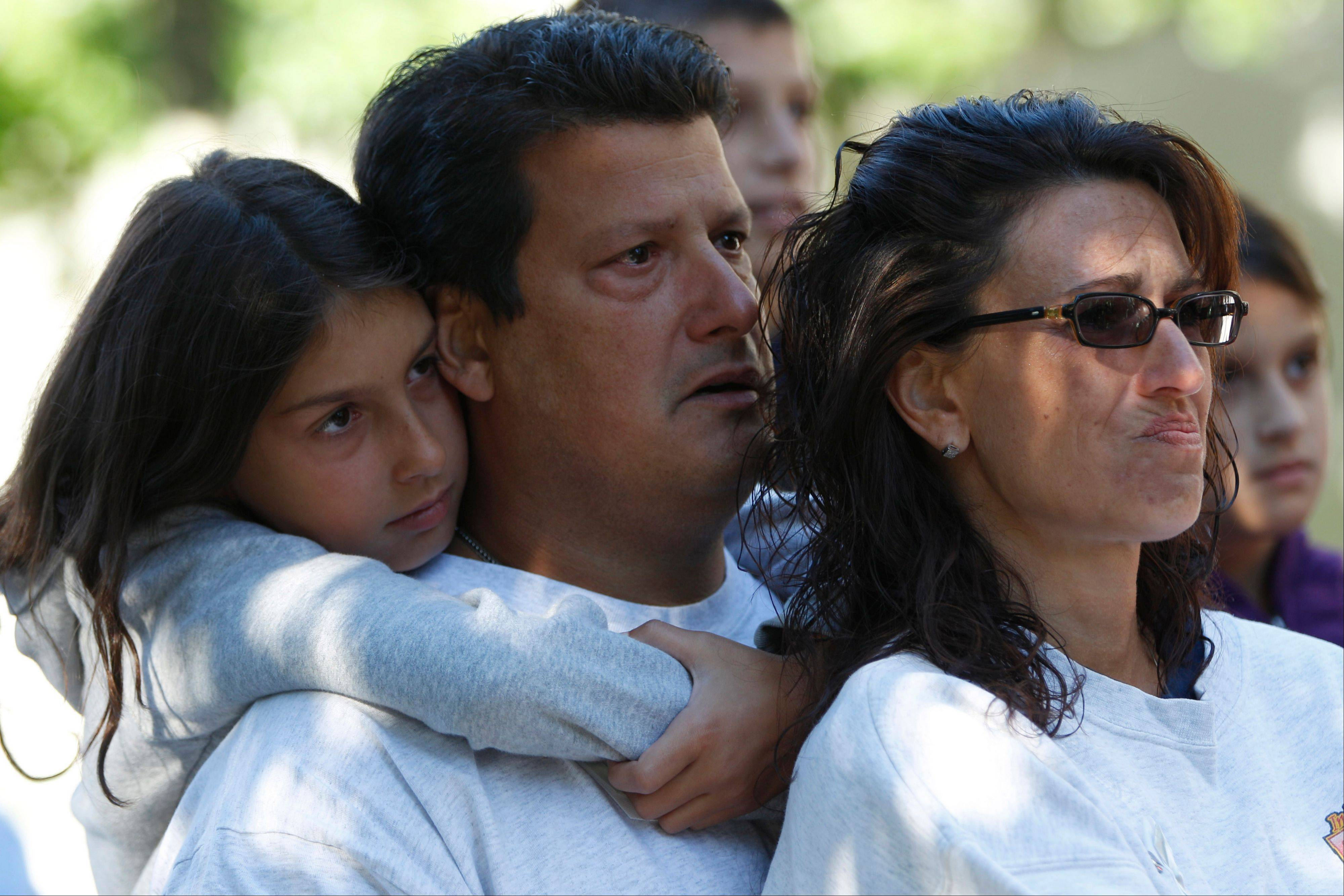 Sofia, Dominick, and Maureen Esposito, left to right, listen as the name of their relative Frankie Esposito is read during the observance of the 11th anniversary of the attacks on the World Trade Center, Tuesday, Sept. 11, 2012 in New York.