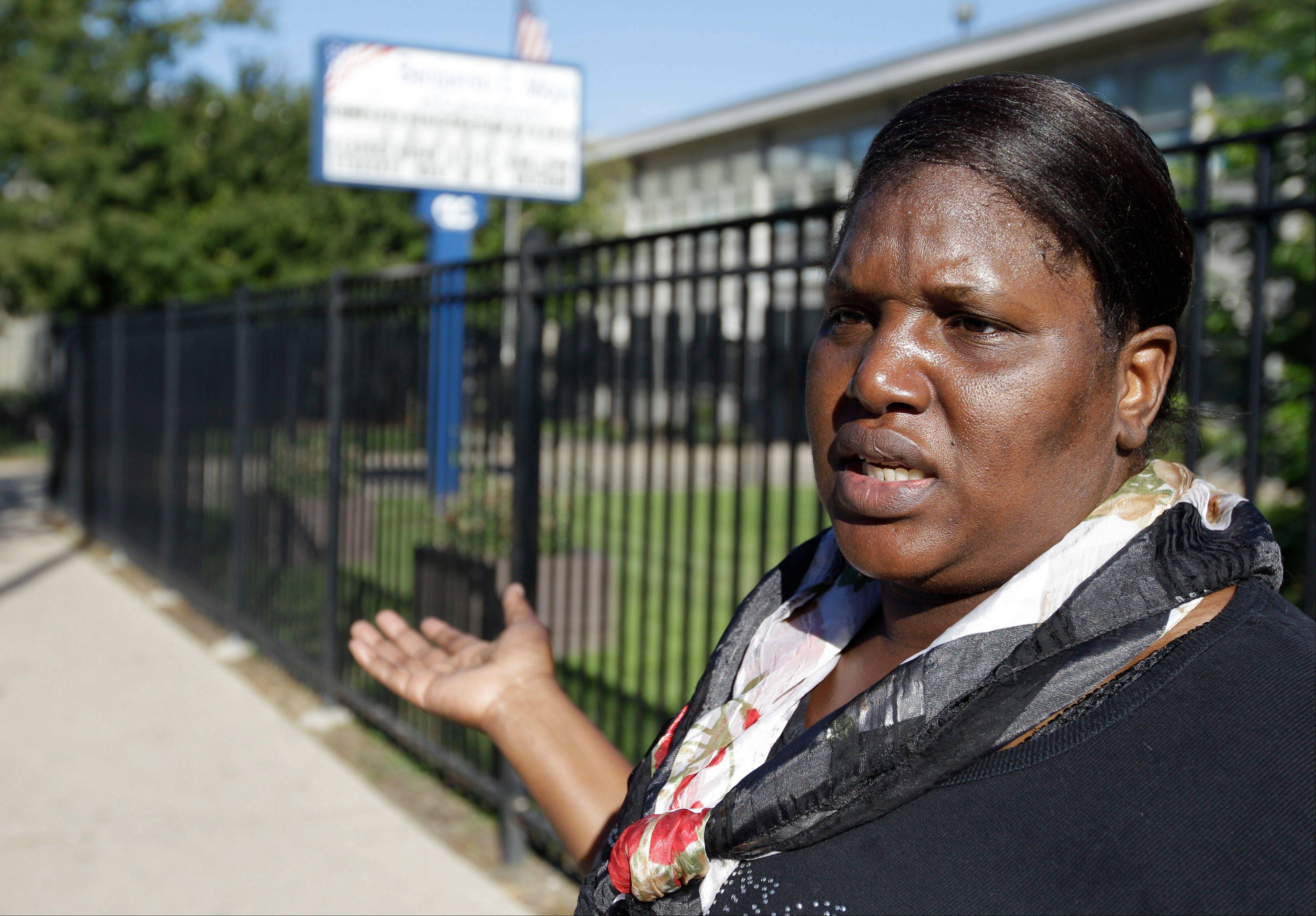 Rose Davis speaks outside Benjamin E. Mays Academy where she dropped off her two grandchildren for a half day of school supervision, during the first day of a teachers strike Monday in Chicago. Thousands