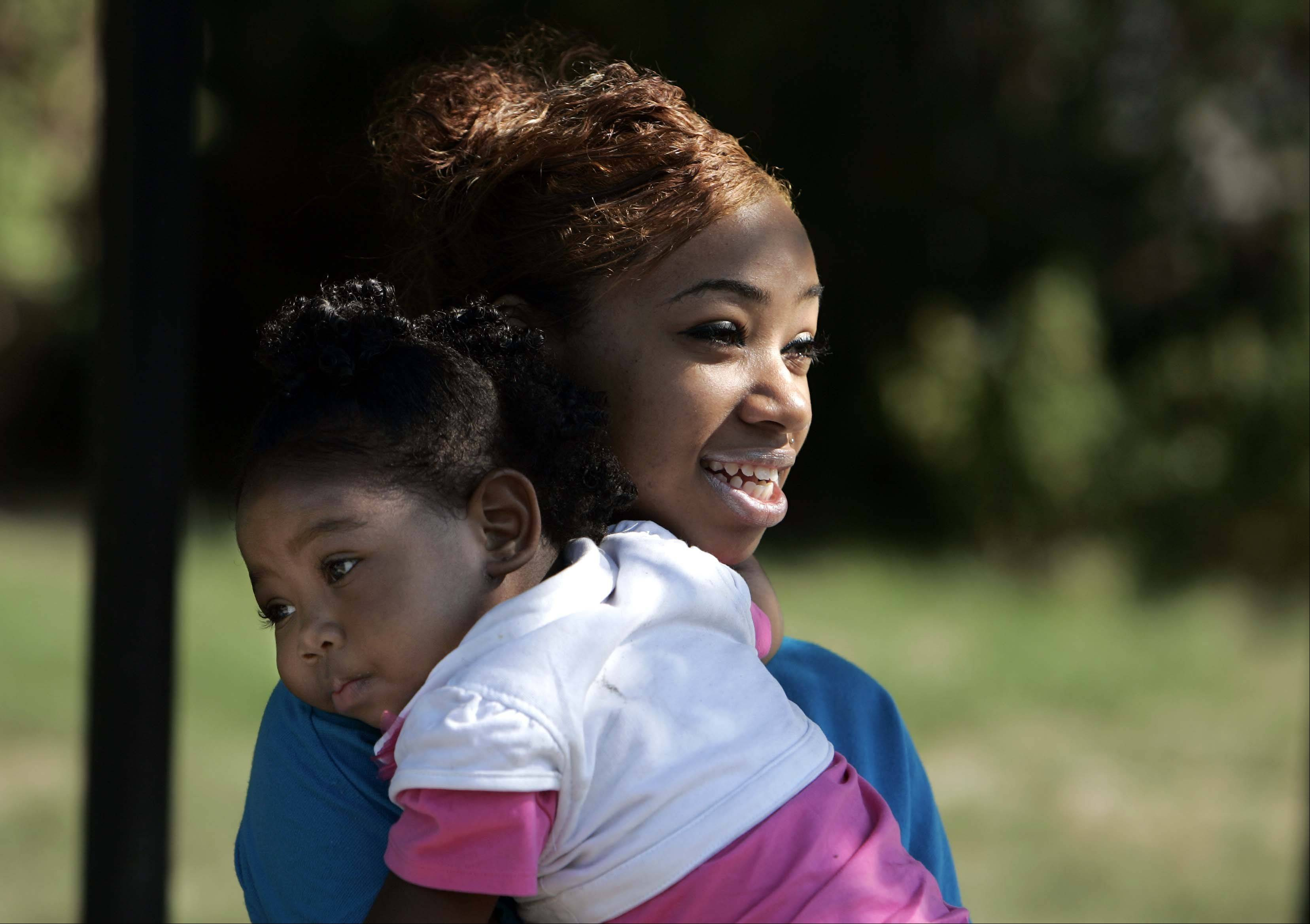 Nineteen-year-old Chrystal Stokes of Elgin with daughter Nevaeh Johnson at their Elgin home. Stokes found out she was pregnant as a sophomore at Elgin High School. She plans to attend Elgin Community College in January.