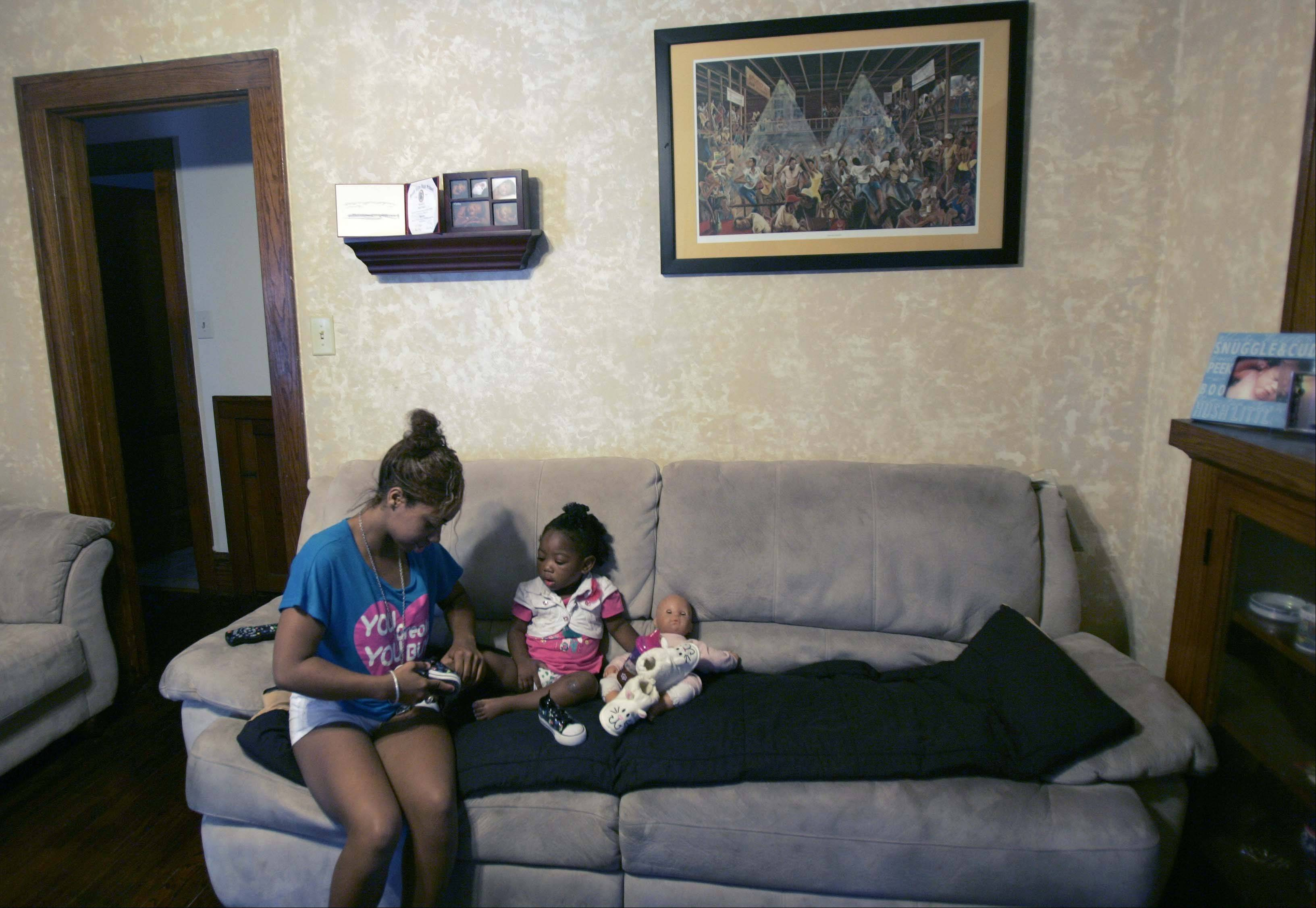 Chrystal Stokes, 19, of Elgin gets her daughter, Nevaeh Johnson, ready for a walk at their home. Stokes found out she was pregnant while she was a sophomore at Elgin High School. Title IX regulations concerning treatment of pregnant and parenting students are part of the reason Stokes was able to graduate. She plans to attend Elgin Community College in January.