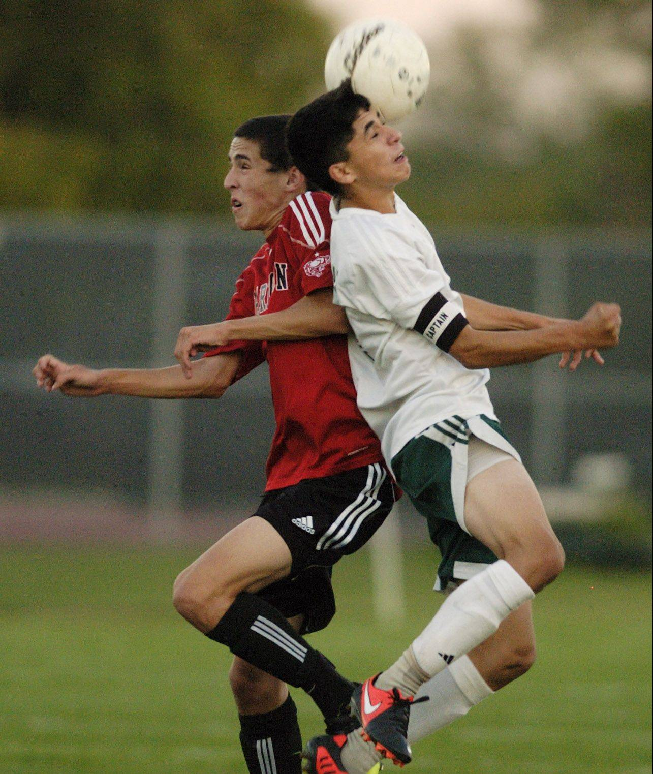Barrington's Logan Morris, left, and Elk Grove's Gio Garcia leap for a header.
