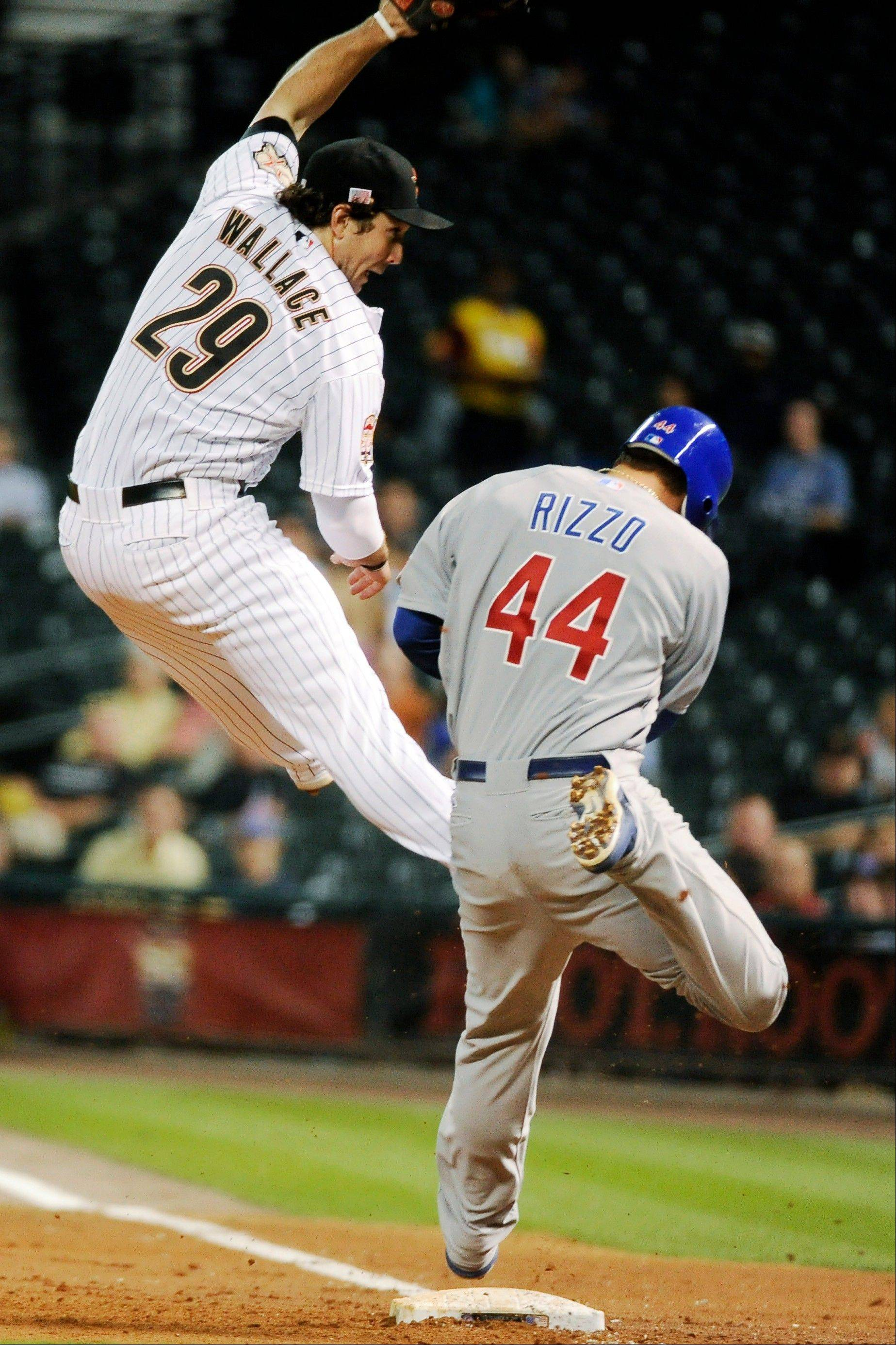 Houston Astros first baseman Brett Wallace comes down on the Cubs' Anthony Rizzo after reaching for a throw in the third inning in Houston. Rizzo went down and was helped from the field.