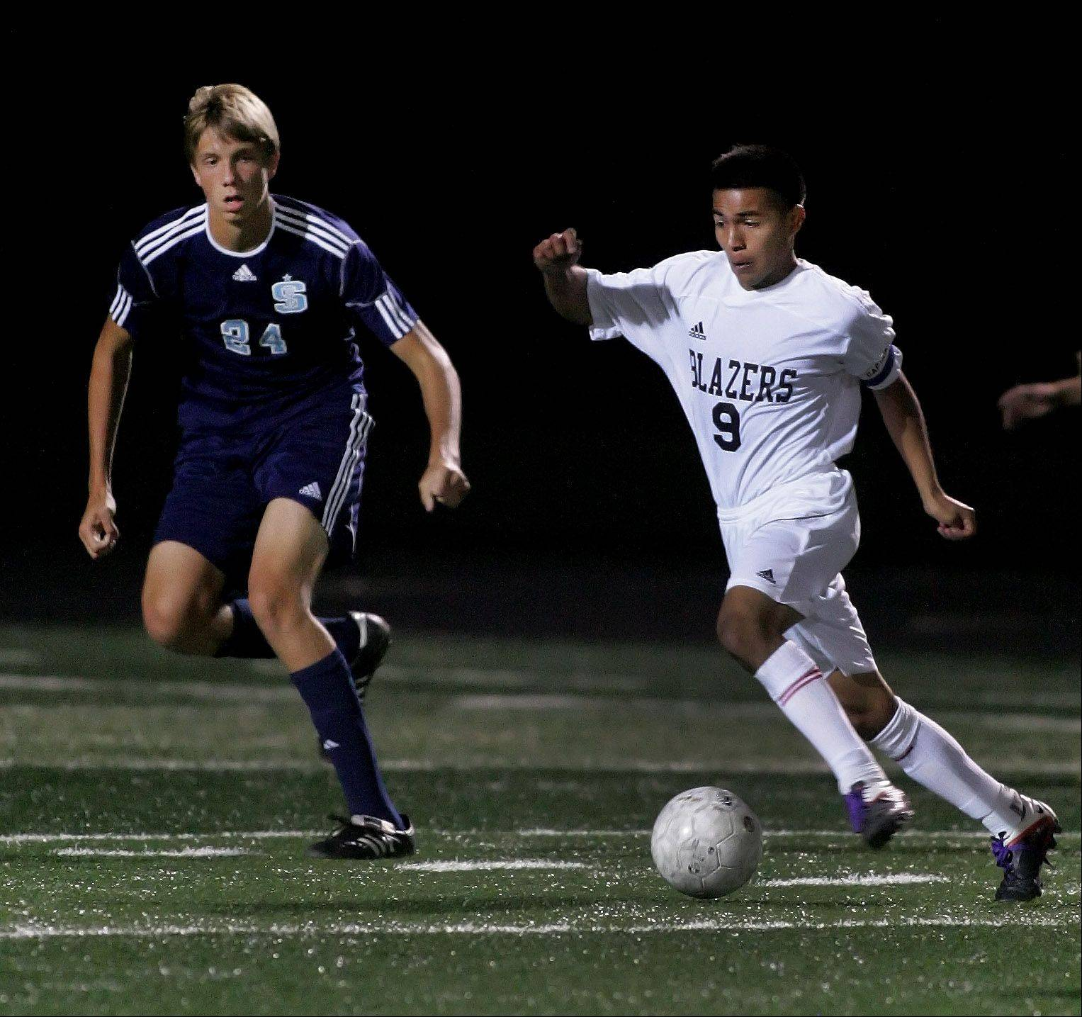 Javier Rodriguez of Addison Trail takes control of the ball from David Drews, left, of Downers Grove South in boys soccer action on Tuesday in Addison.