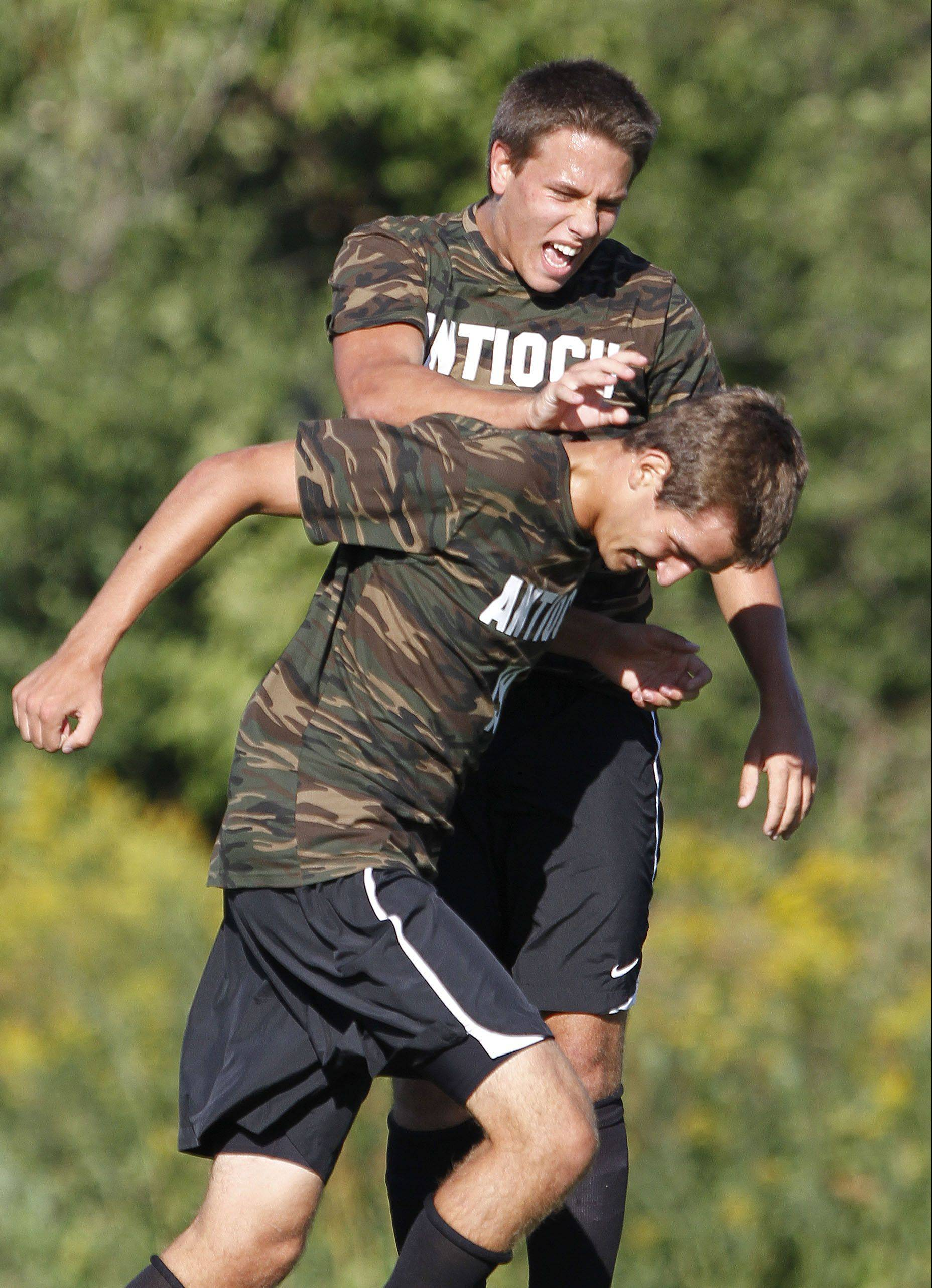 Antioch's Erik VanTreeck, left, congratulates Nick Brito after he scored in the first half Tuesday at Lakes.