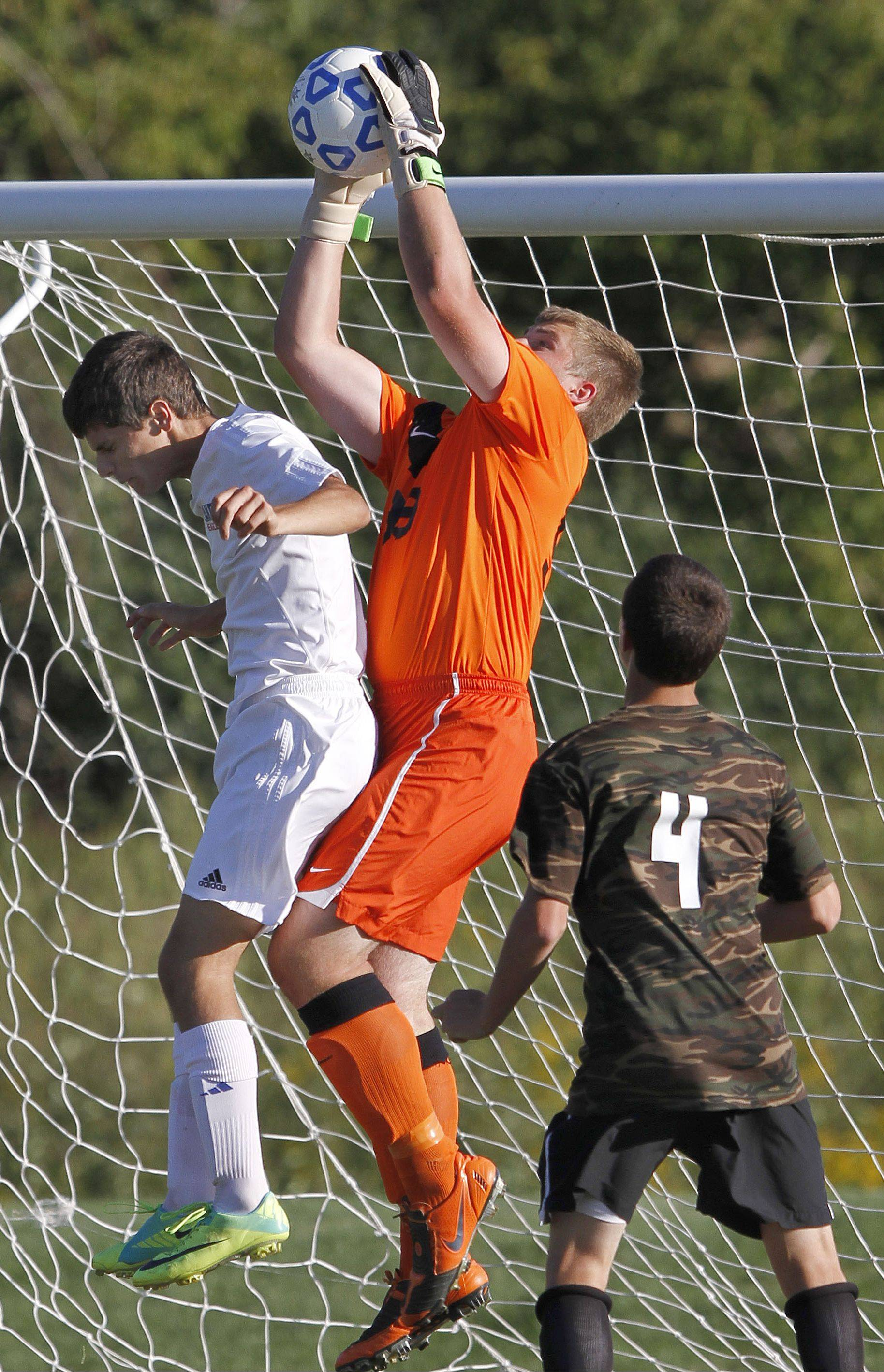 Antioch goalie Tommy Tritschler, middle, goes up for a ball with Lakes' Joey Savino as Antioch's Thomas Furlong looks on Tuesday at Lakes.