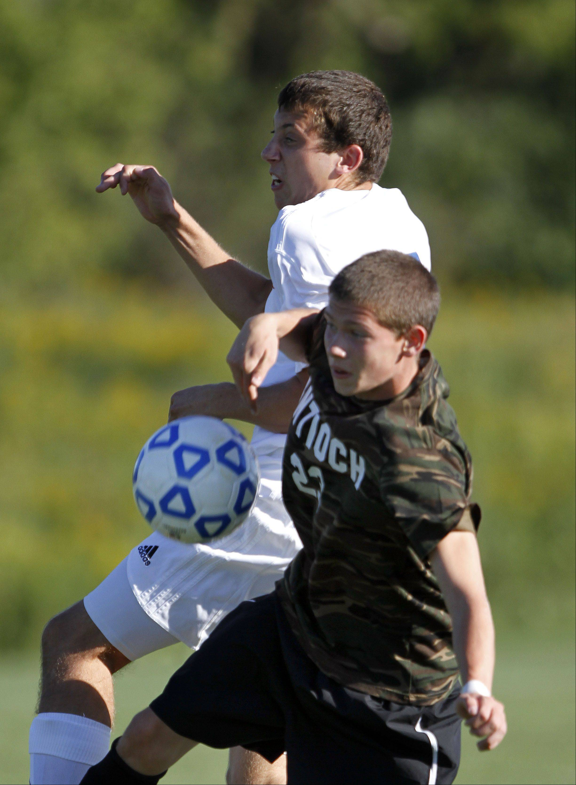 Lakes' Nichlaus Powell, left, and Antioch's Krystian Streit battle for the ball Tuesday at Lakes.