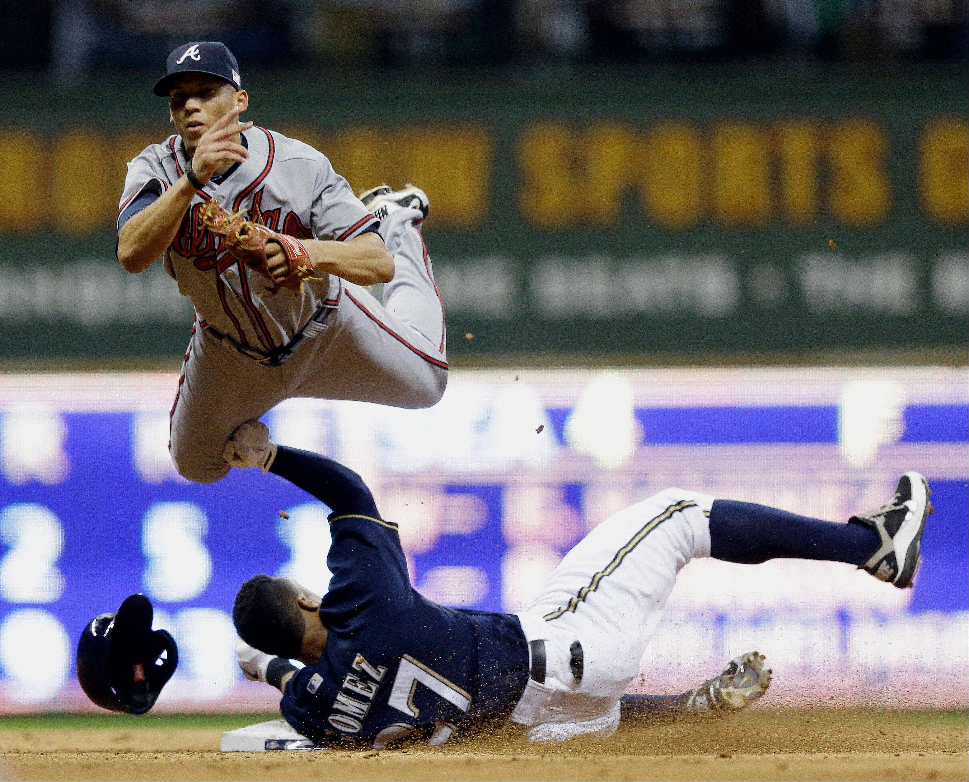 Atlanta's Andrelton Simmons leaps over Milwaukee's Carlos Gomez as he tries to turn a double play on a ball hit by Jean Segura during the seventh inning Tuesday in Milwaukee. Segura beat the throw.