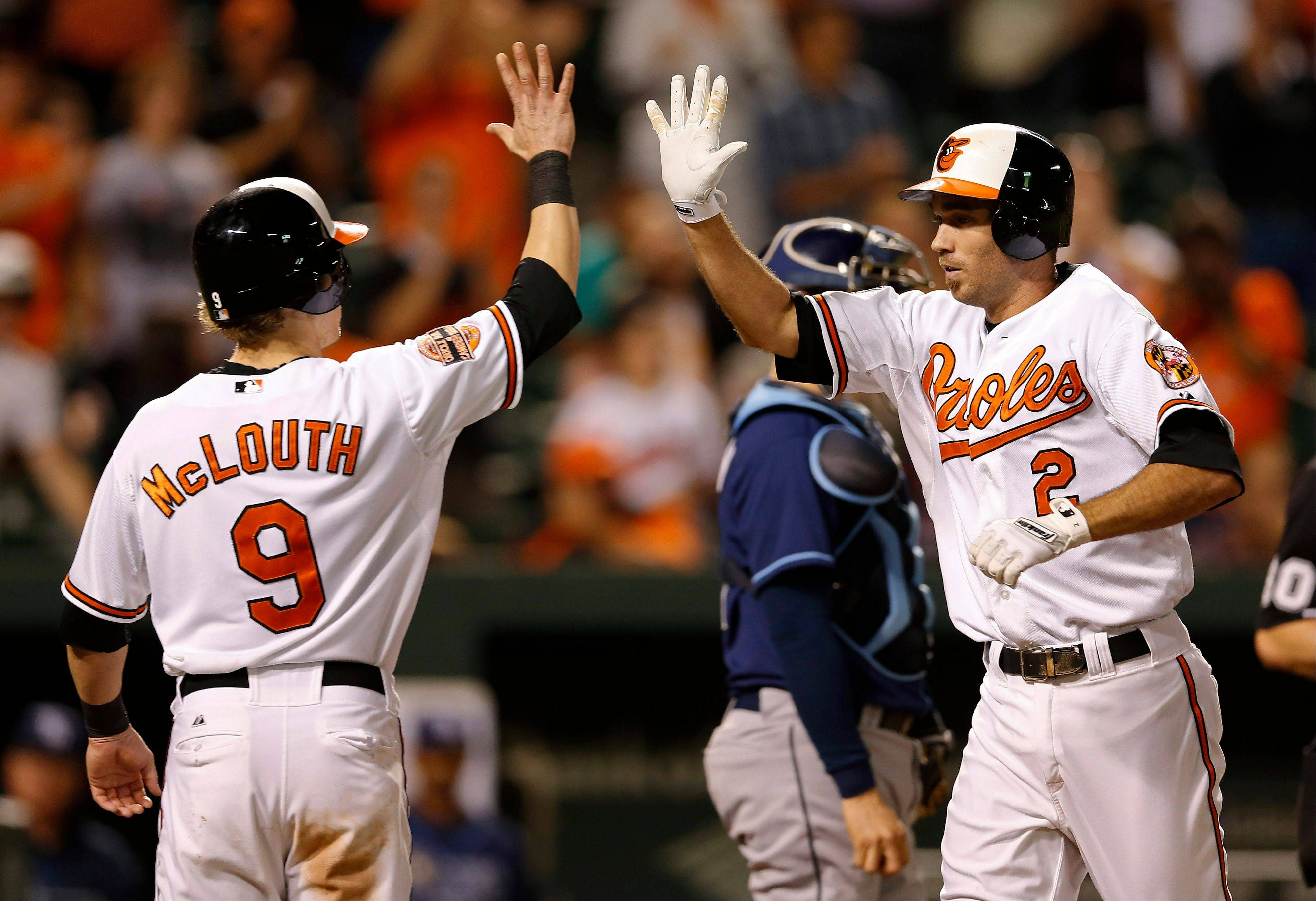 Baltimore's J.J. Hardy, right, high-fives teammate Nate McLouth after driving him in on a home run in the eighth inning Tuesday at home against Tampa Bay.