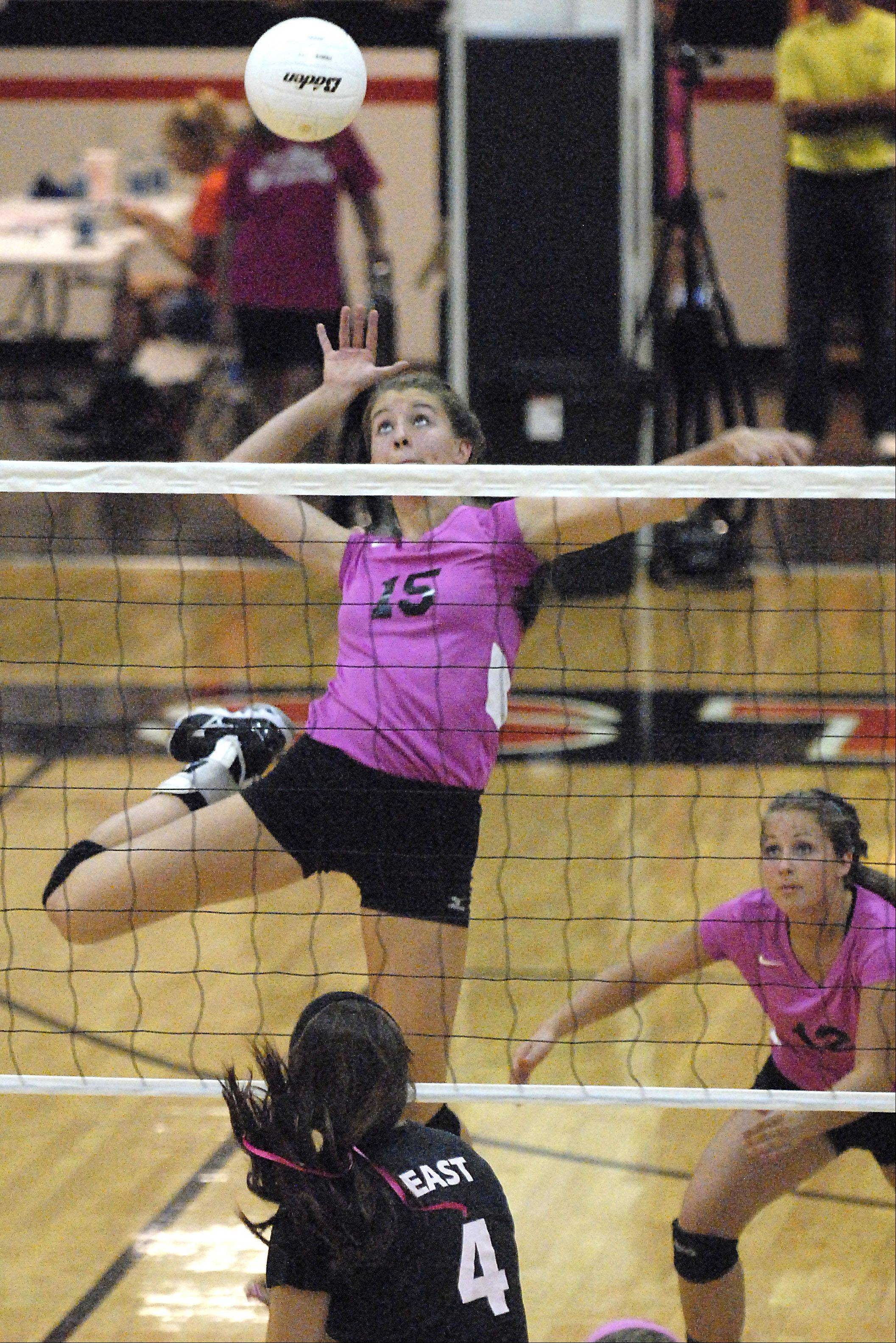 St. Charles North's Alex Stone spikes the ball over the net and head of St. Charles East's Caitlyn Ballard.