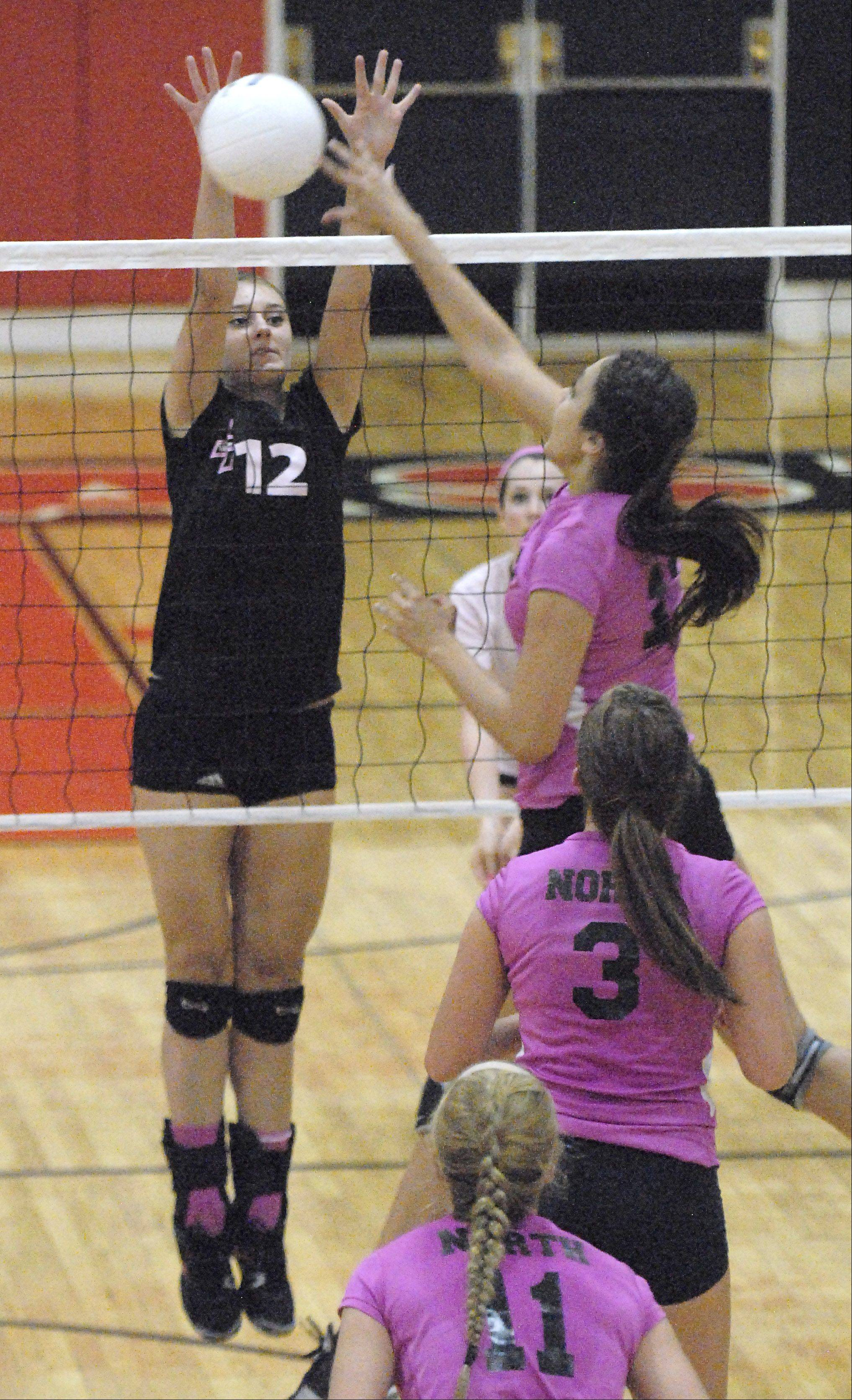 St. Charles North's Sophia DuVall tips the ball over to St. Charles East's Ashley Bullock in game two on Tuesday, September 11.