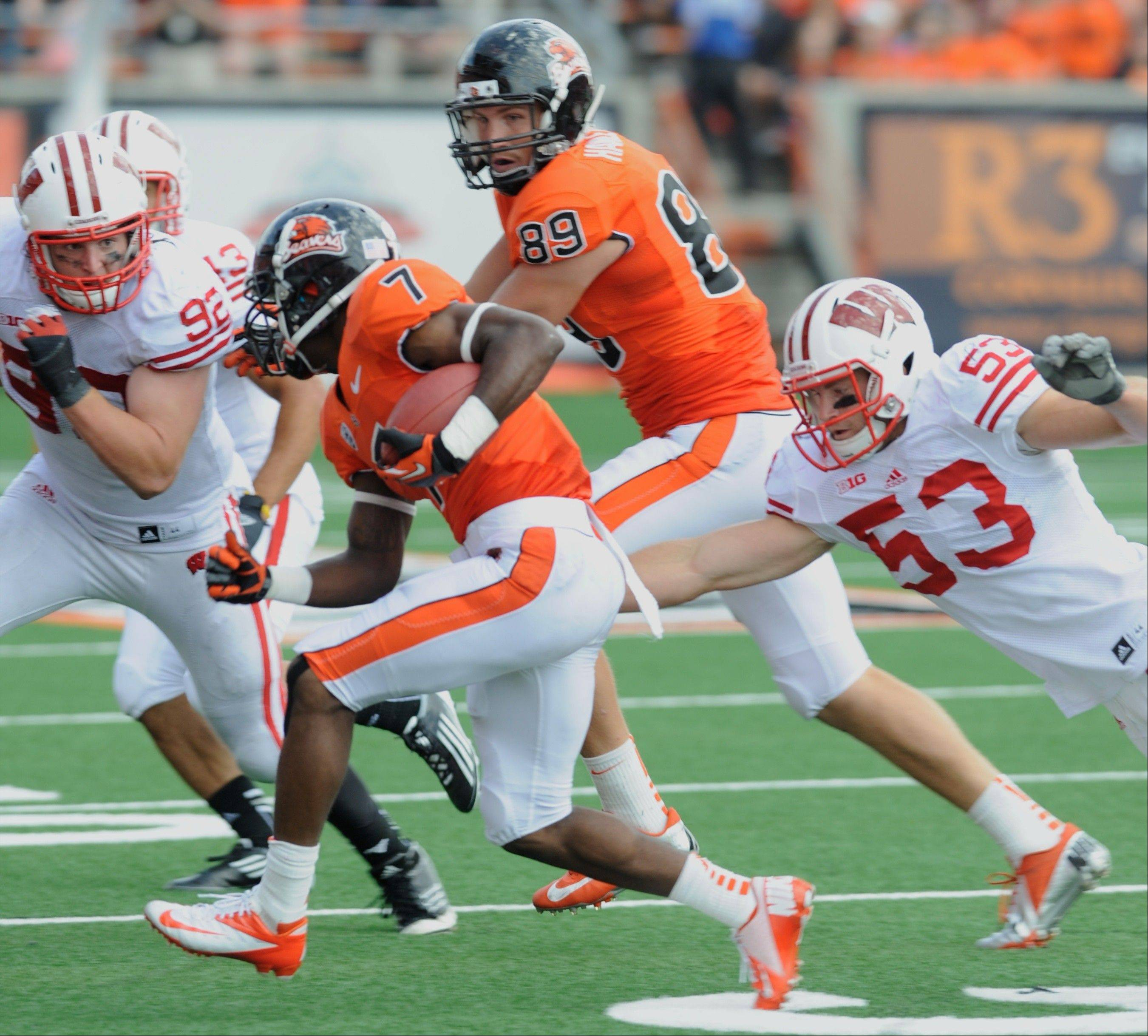 Oregon State's Brandin Cooks (7) runs against Wisconsin's Mike Taylor (53) and Pat Muldoon (92) Saturday during the second half. The Big Ten went 6-6 last week, with Wisconsin and Nebraska both losing to Pac-12 teams.
