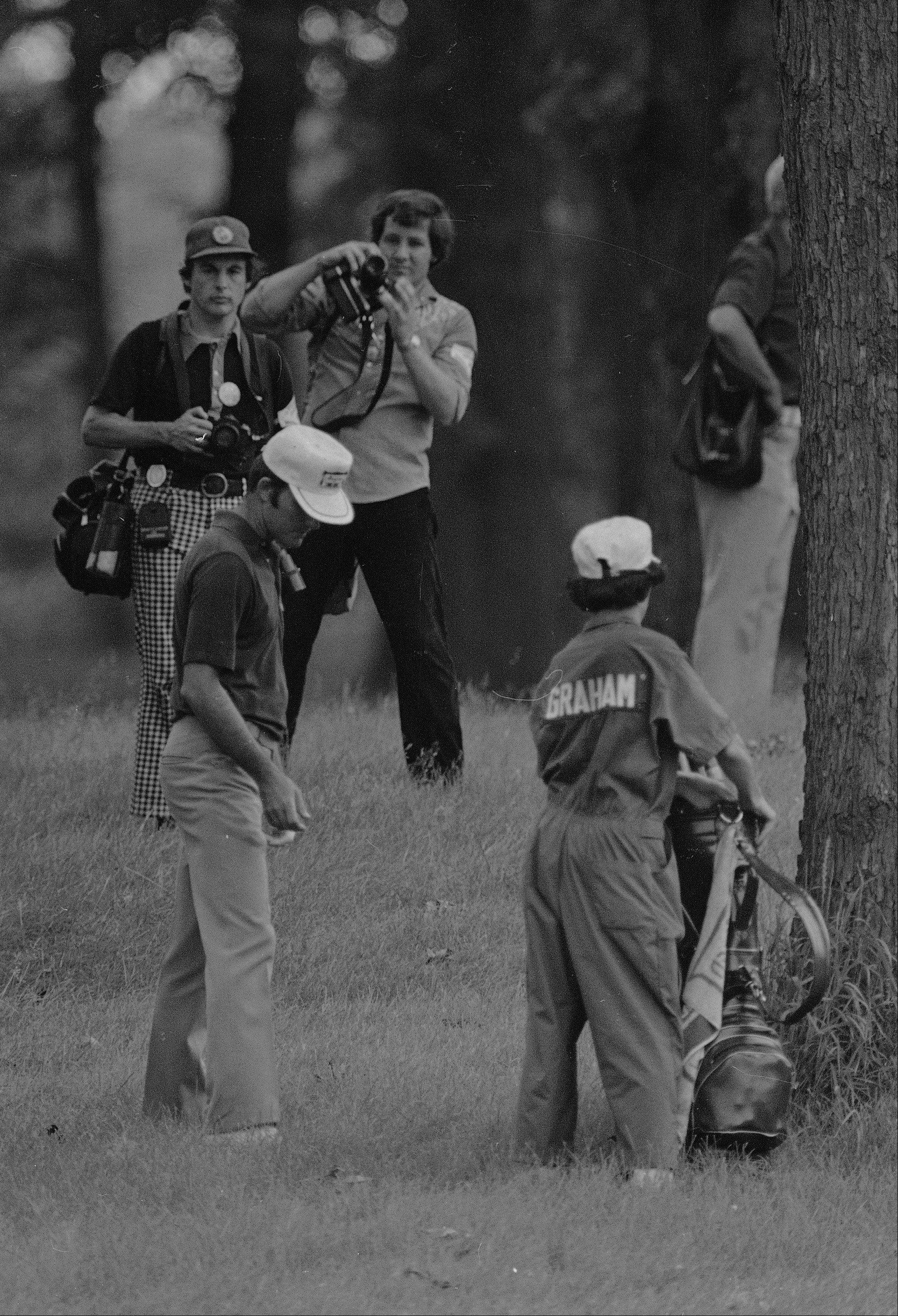 Deep in the rough behind a tree, Lou Graham studies his ball and a way to solve his problem on the 13th fairway of Medinah, June 23, 1975. He punched it out close to the green, pitched up and one putted for his par. He went on to win the U.S. Open championship over John Mahaffey, Jr., by two strokes.