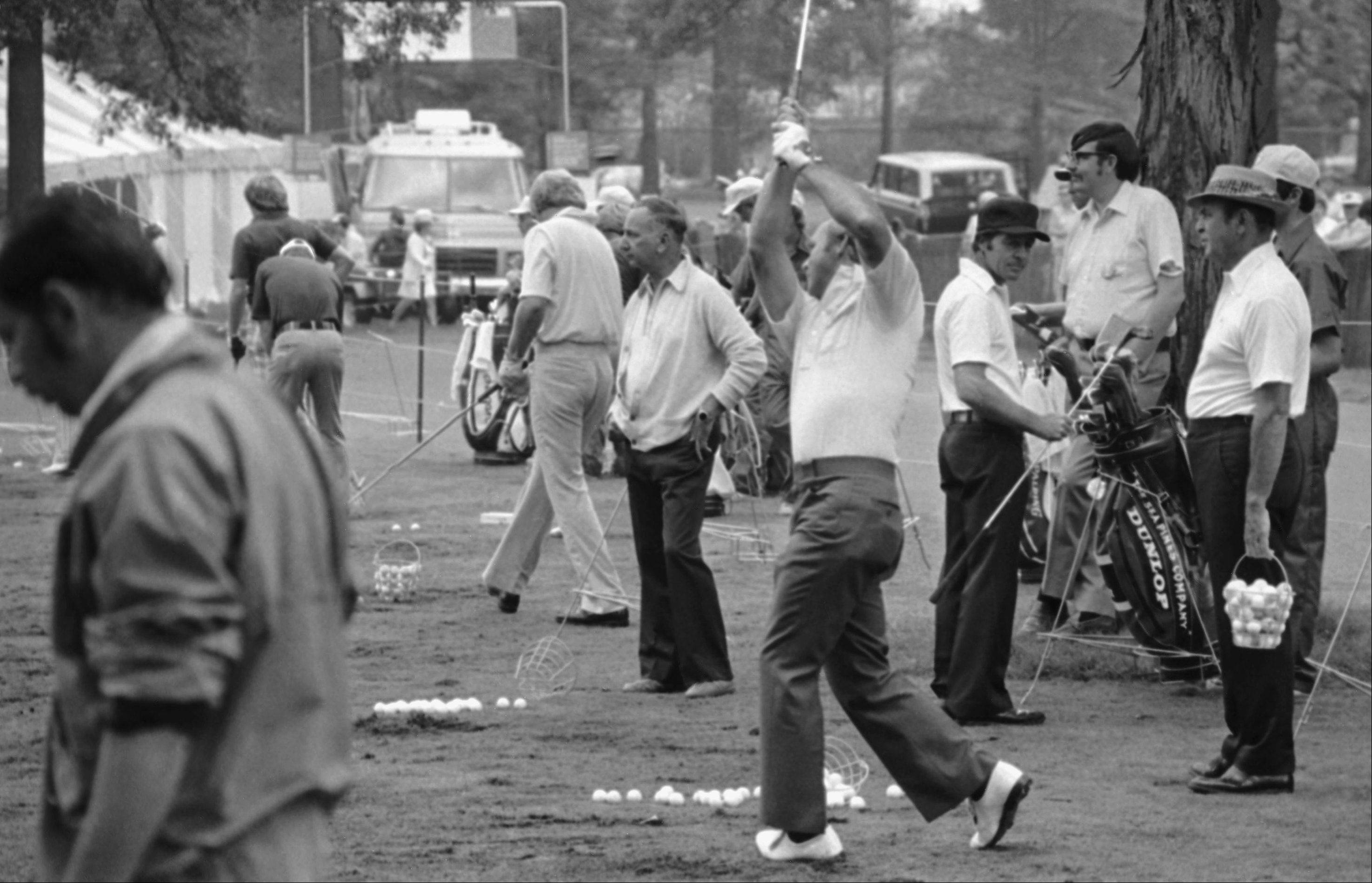 While Arnold Palmer, center, hits from the practice tee at Medinah Country Club, Tuesday, June 17, 1975, Medinah, Ill. Gary Player of South Africa, dark cap, and veteran Sam Sneed, holding a bucked of ball at right, await their turn to get in some practice swings.