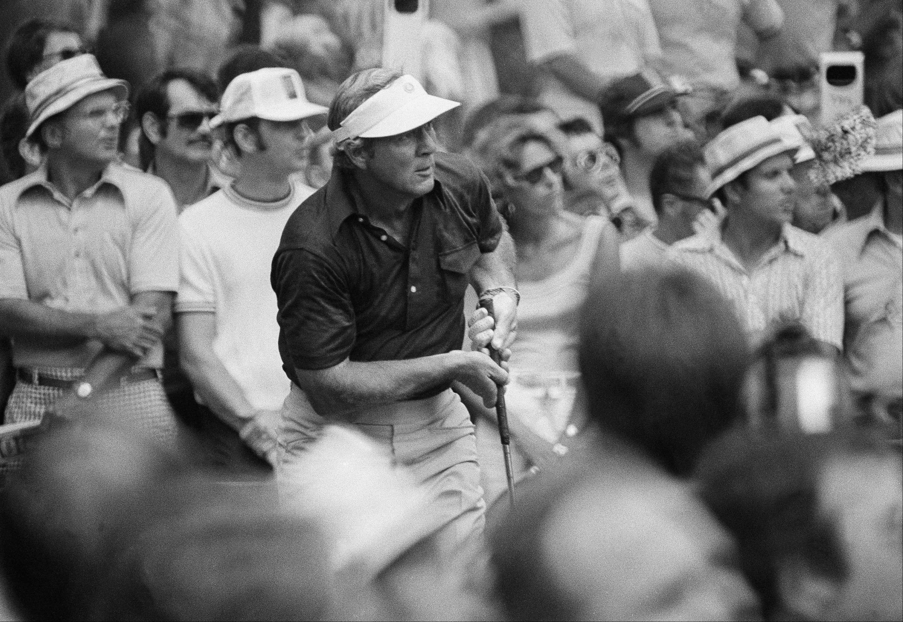 The crowd of spectators at Medinah Country Club in Illinois seems to be pressing in on Arnold Palmer of Ligonier, Pa., as he tees off in the first round of the U. S. Open, June 19, 1975.