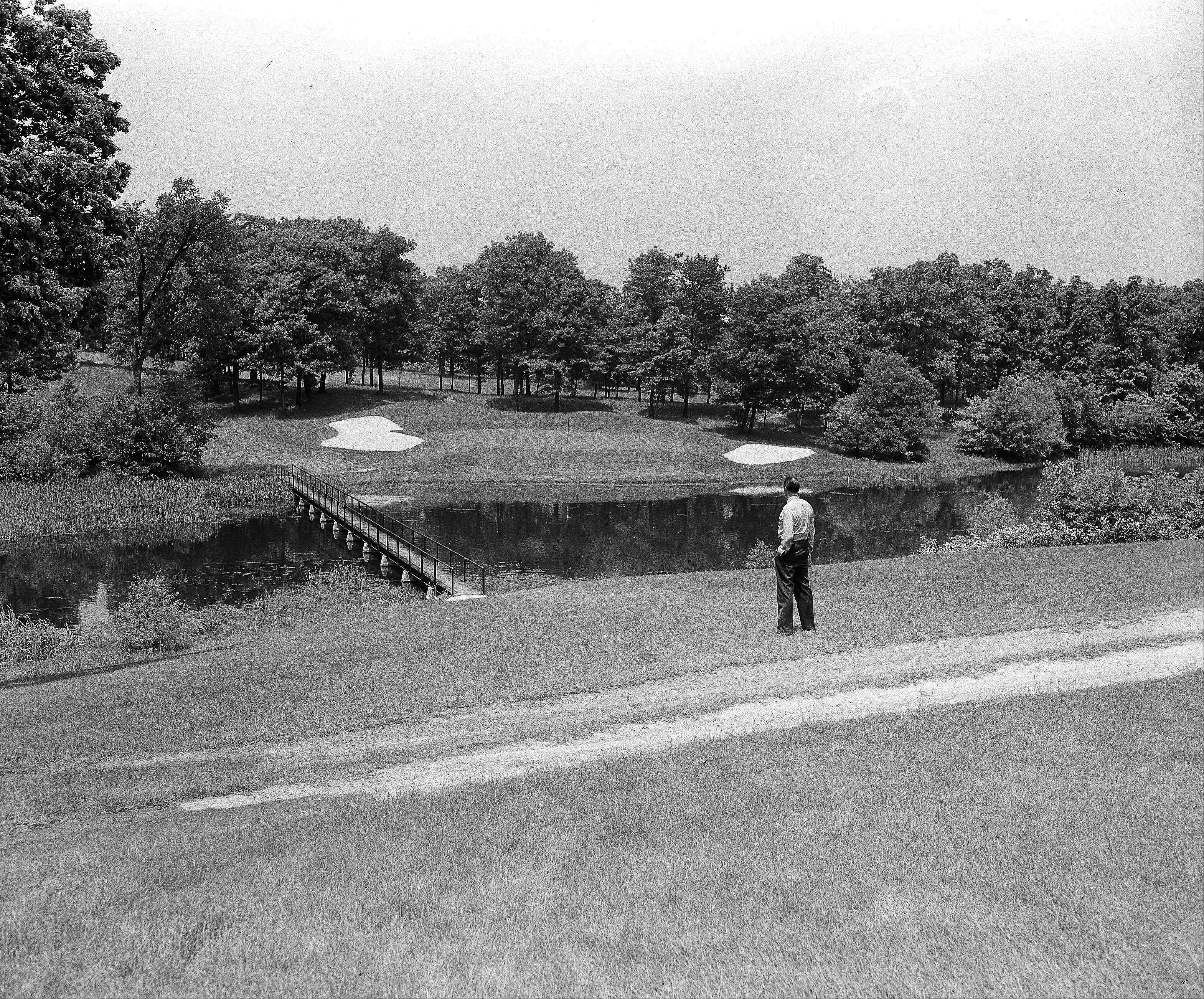 A spectator views the picturesque setting at the 17th hole of the No. 3 Championship Course at Medinah Country Club, Medinah, Illinois on May 31, 1949, where the U.S. Open Golf Tournament will be held June 9-11. Sand traps, a water hazard and an elevated green are among the obstacles golfers will have to contend with on the 193-yard, par 3 hole.
