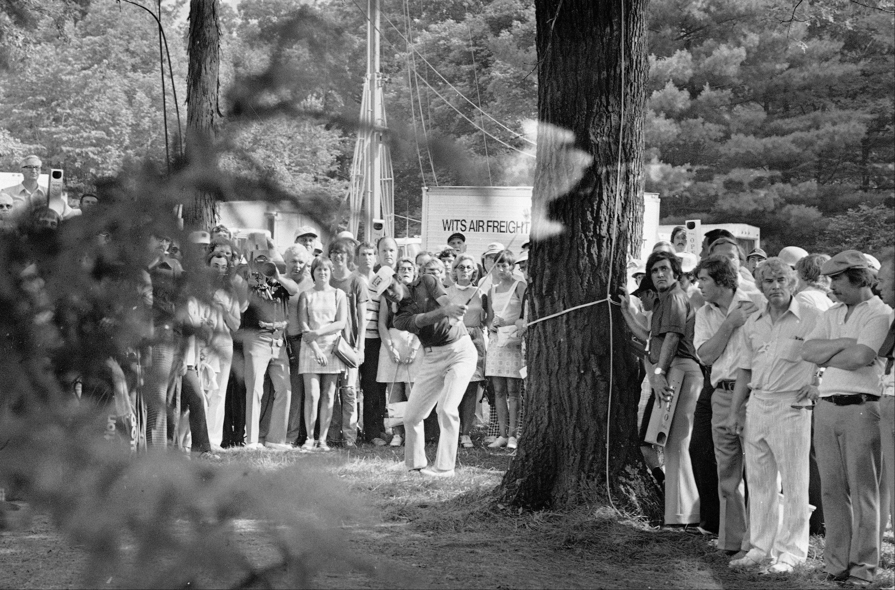 Hitting from the rough in the trees, Lou Graham hits his second shot on Medinah's 18th hole in the playoffs of the U.S. Open, June 23, 1975. The shot landed on the green and Lou went on to par the hole and win the Open by one stroke.