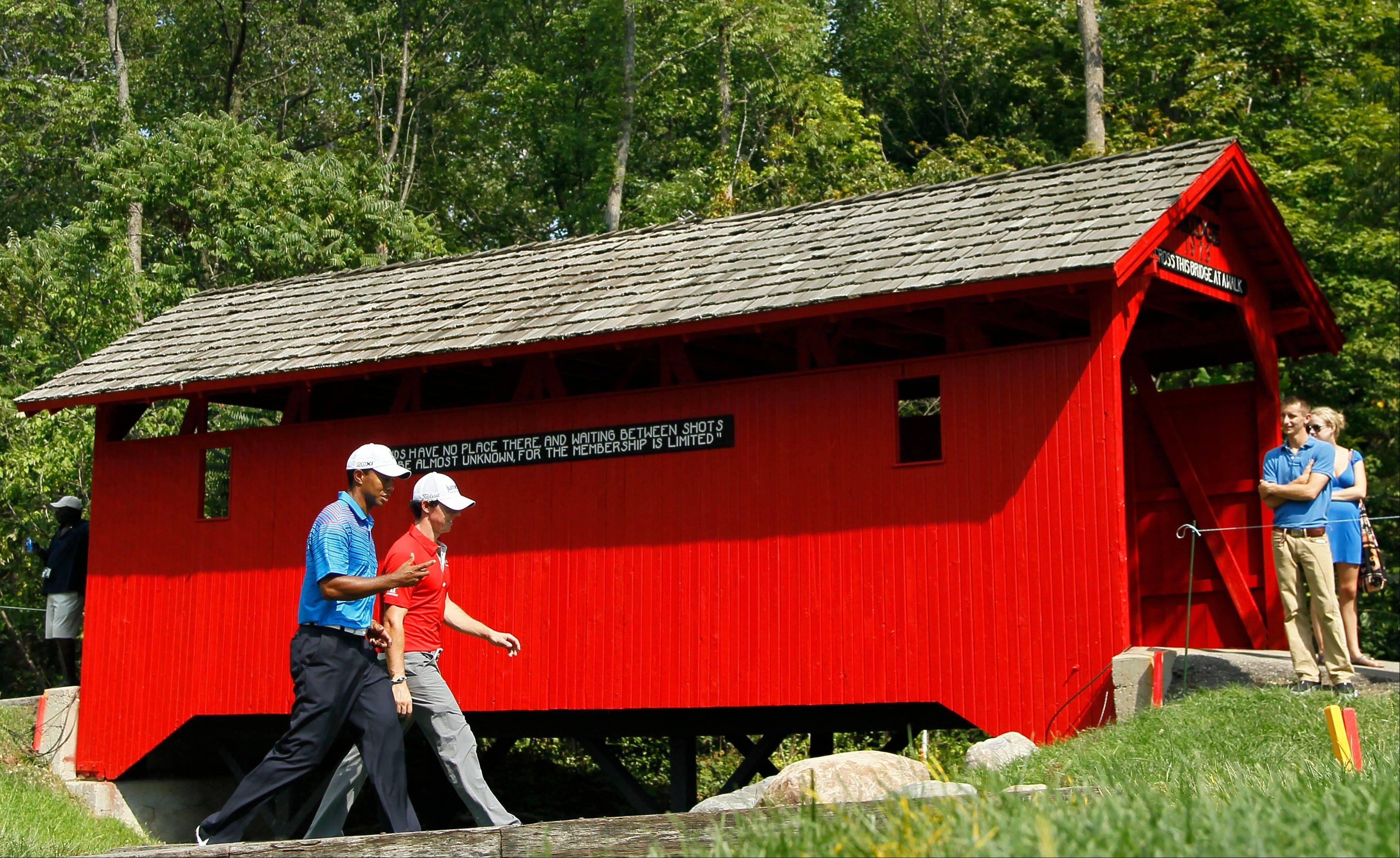 Tiger Woods, left, and Rory McIlroy, of Northern Ireland, here walking past the covered bridge at the sixth hole during the first round of the BMW Championship at Crooked Stick Golf Club in Carmel, Ind., should see a lot of each other during the 2012 Ryder Cup at Medinah Country Club Sept. 28-30.