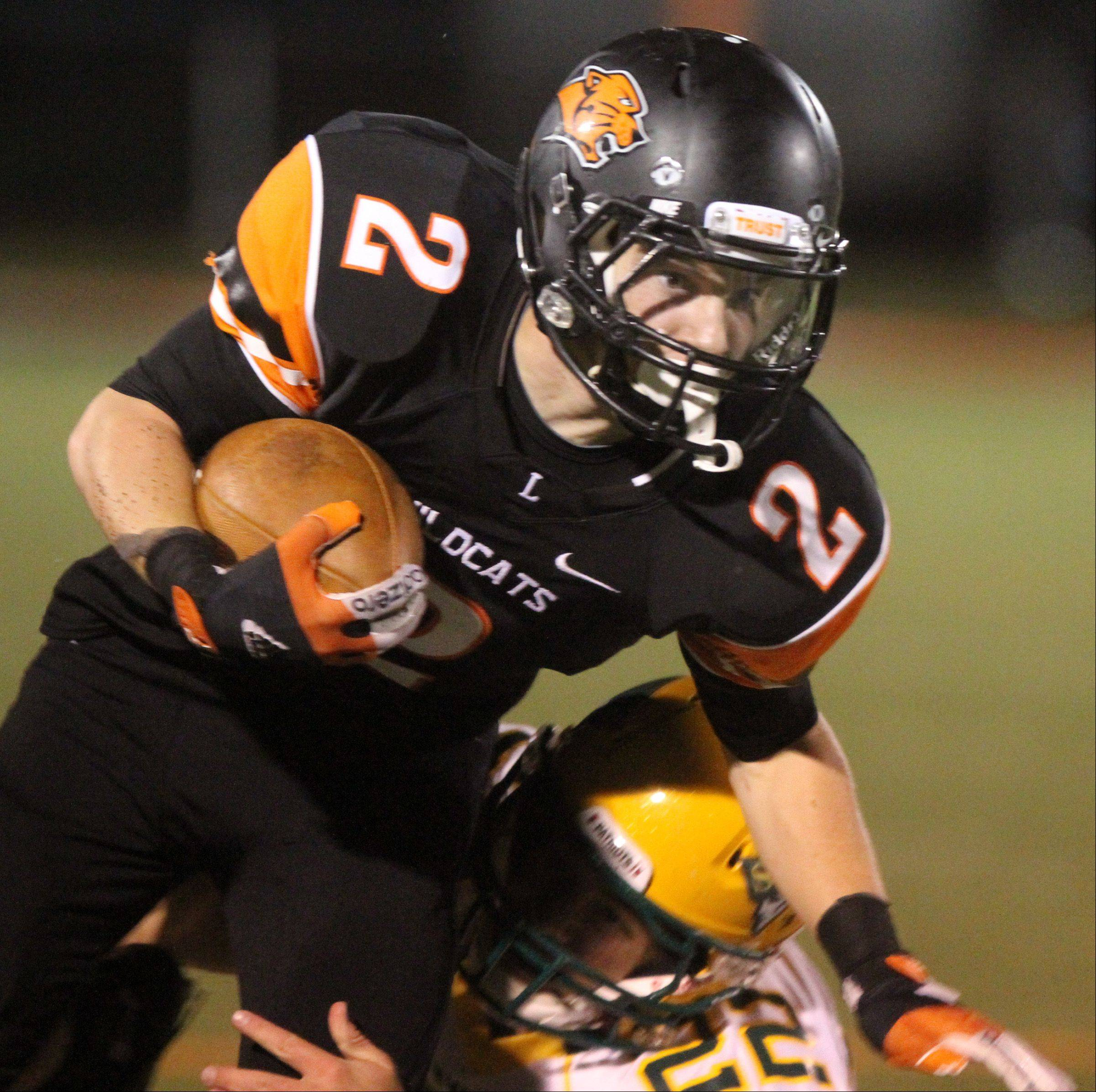 Libertyville running-back Conor Simpson tucks the ball in against Stevenson defender Timmy Breen at Libertyville on Friday.