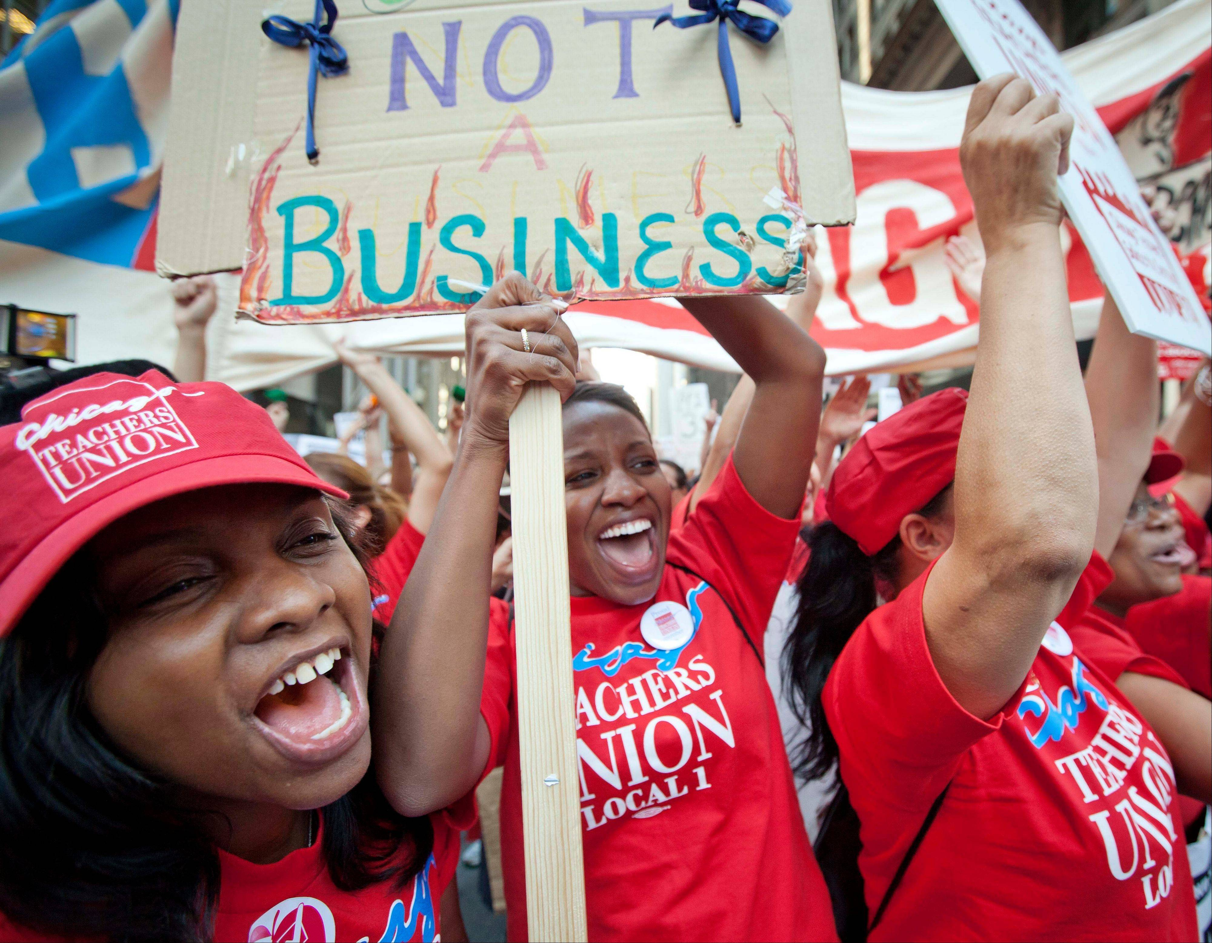 Public school teachers cheer as Chicago Teachers Union President Karen Lewis, unseen, arrives unexpectedly to address a rally of thousands of teachers gathered for the second consecutive day outside the Chicago Board of Education district headquarters on Tuesday, Sept. 11, 2012 in Chicago.