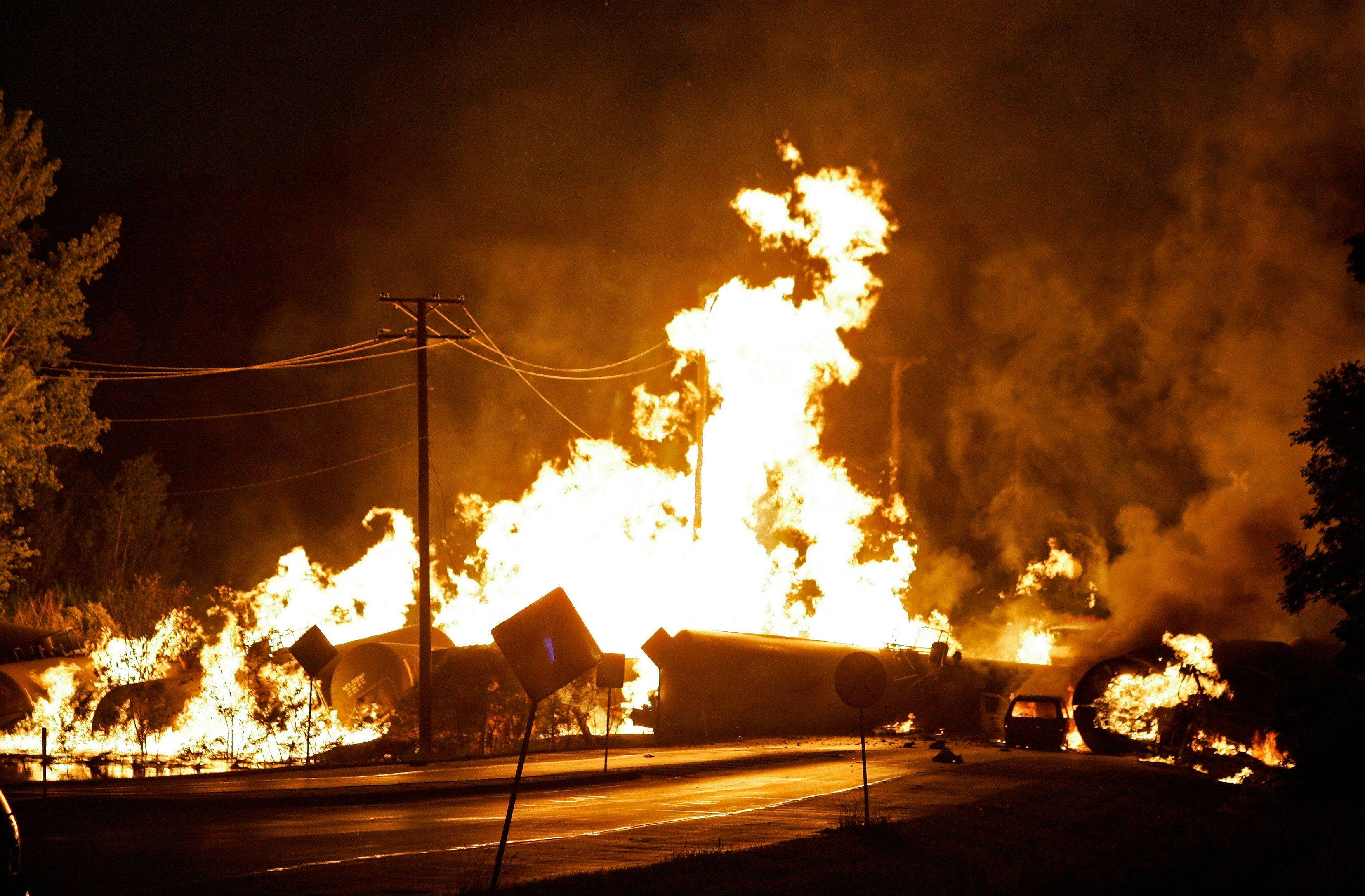In this June 19, 2009 file photo, a car is seen engulfed in flames from rail cars loaded with ethanol that derailed in Rockford, Ill. A Rockford woman died as she tried to flee the derailment. For two decades, one of the nation's most common types of rail tanker, known as a DOT-111, has been allowed to haul hazardous liquids from coast to coast even though transportation officials were aware of a dangerous design flaw that almost guarantees the car will tear open in an accident.