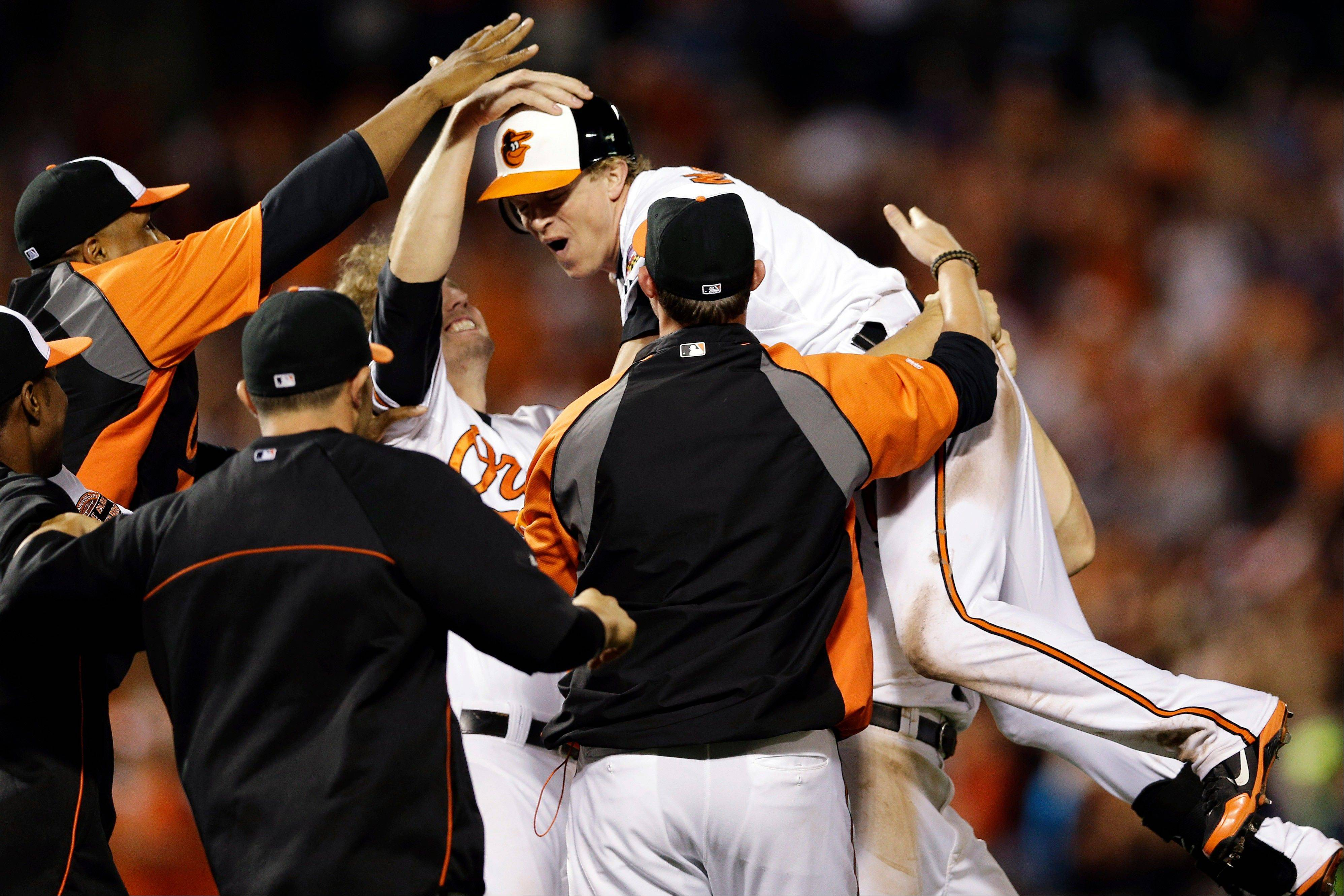 The Orioles' Nate McLouth, center, celebrates with teammates after driving in Manny Machado for the game-winning run Wednesday against the Tampa Bay Rays in Baltimore.