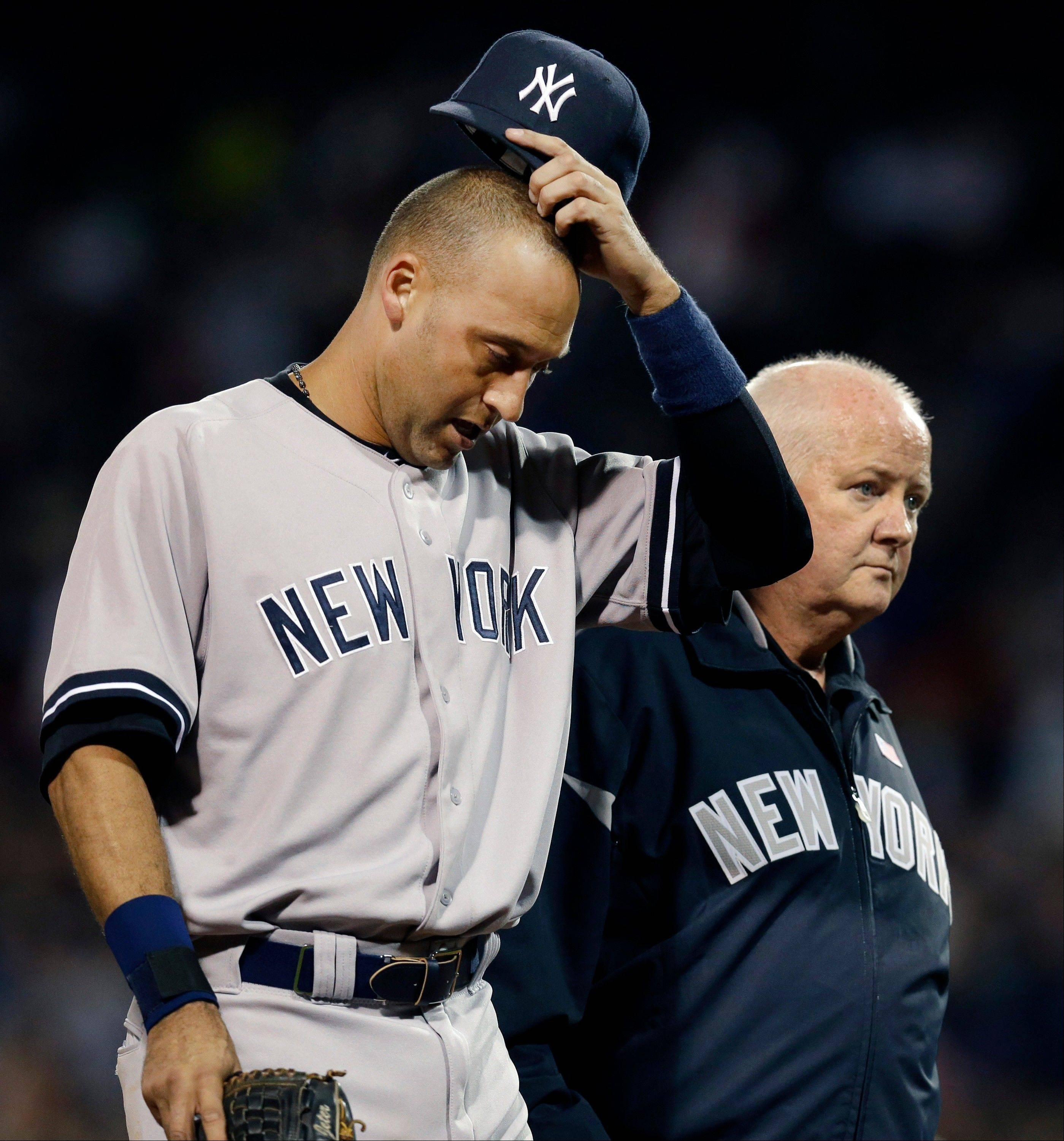 The Yankees� Derek Jeter leaves the game with team trainer Steve Donohue after he was injured trying to beat out a double-play grounder during the eighth inning Wednesday in Boston.