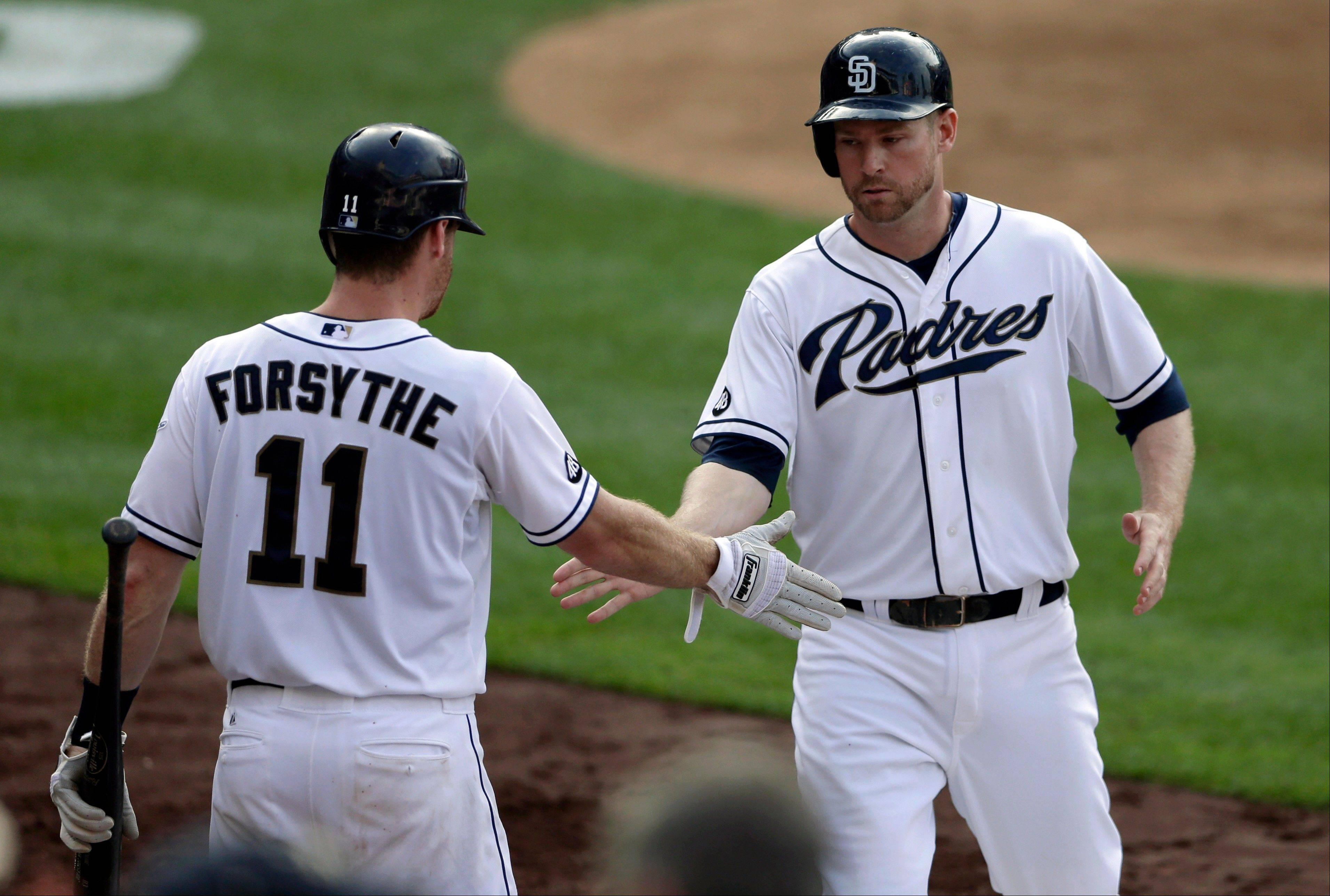 The Padres' Chase Headley, right, is congratulated by teammate Logan Forsythe (11) after Headley scored during the sixth inning Wednesday at home against the Cardinals.