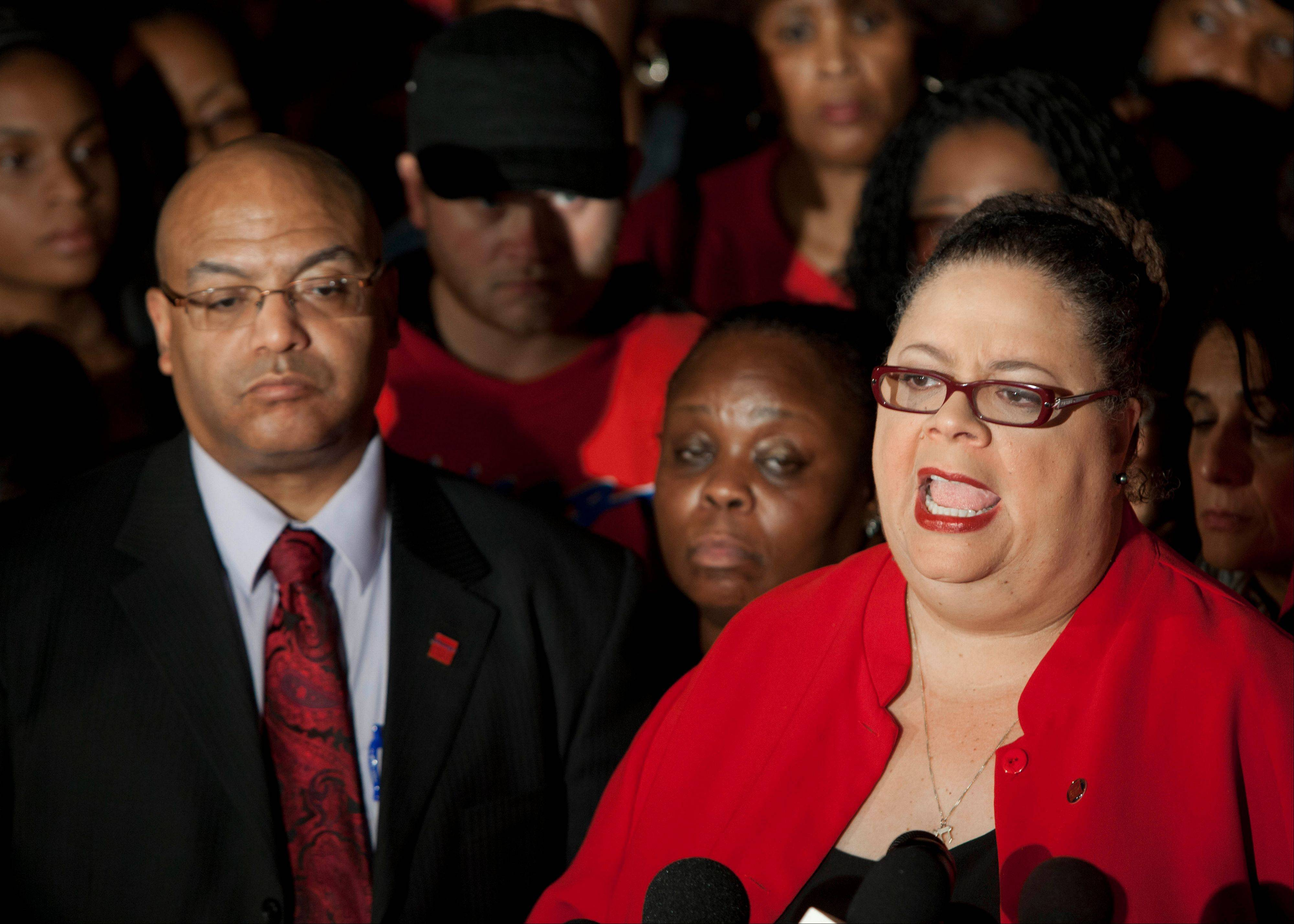 On Sunday night, Chicago Teachers Union President Karen Lewis, right, tells reporters outside the union's headquarters that the city's 25,000 public school teachers will walk the picket line Monday morning.