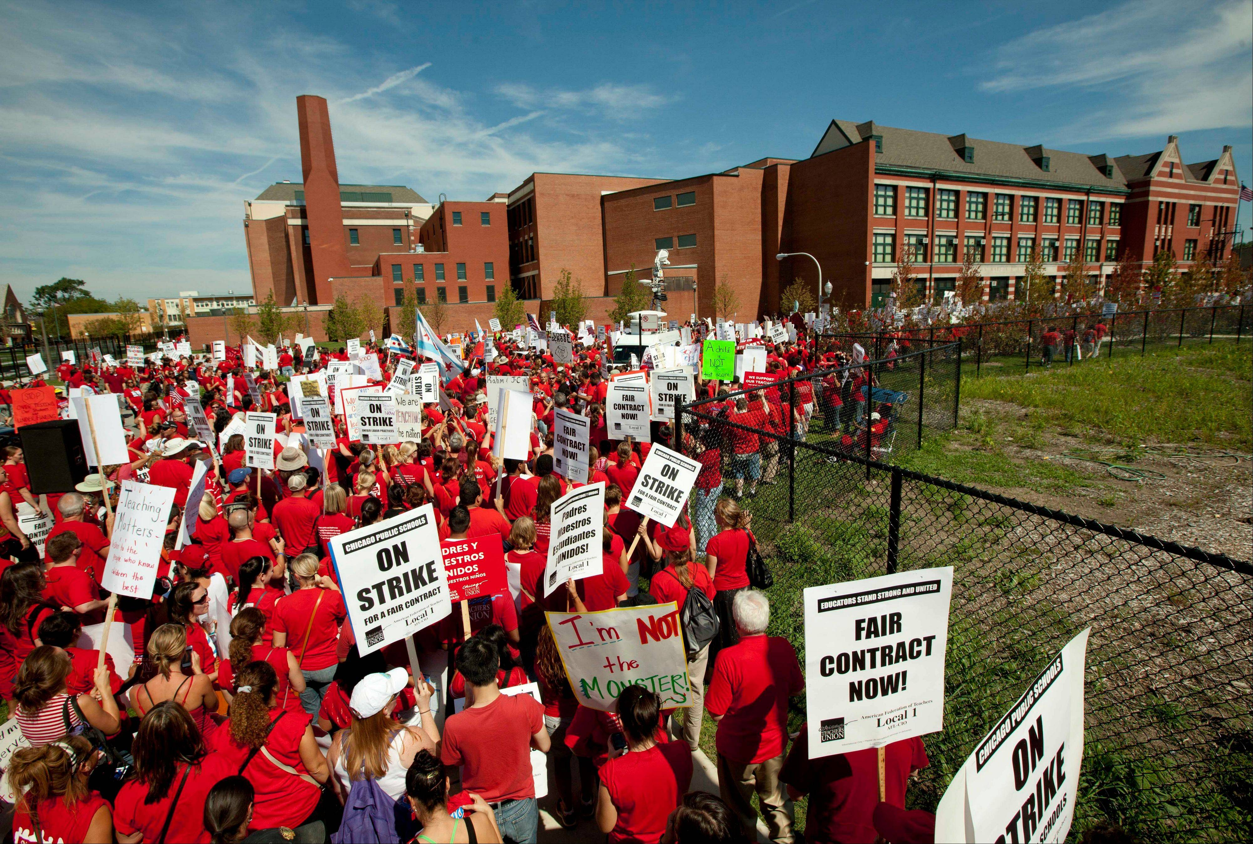A large group of Chicago public school teachers marches past John Marshall Metropolitan High School on Wednesday on the city's West Side.