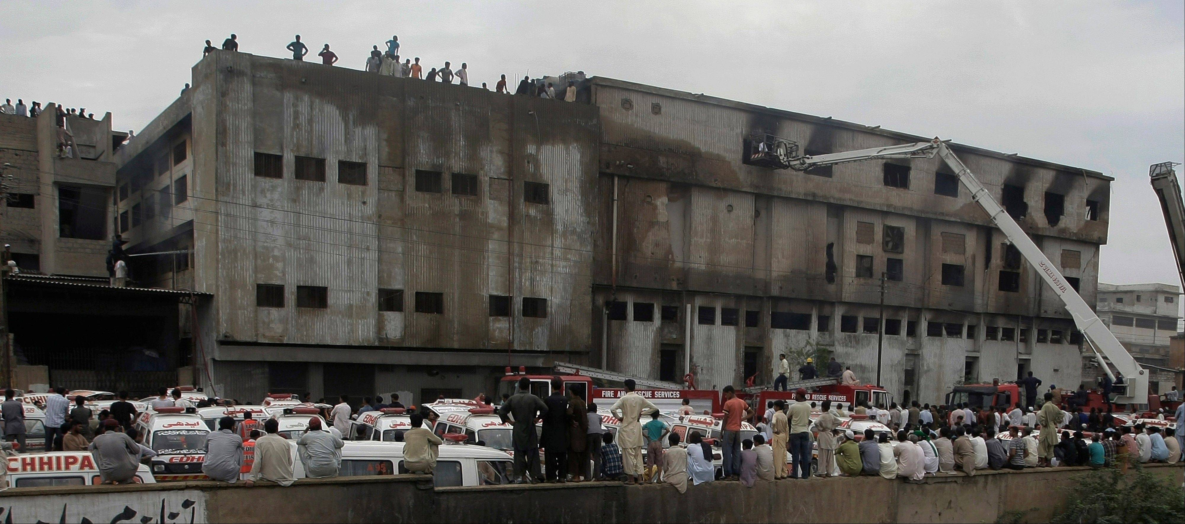 People gather as rescue work is in progress at a burned garment factory in Karachi, Pakistan on Wednesday, Sept. 12, 2012.
