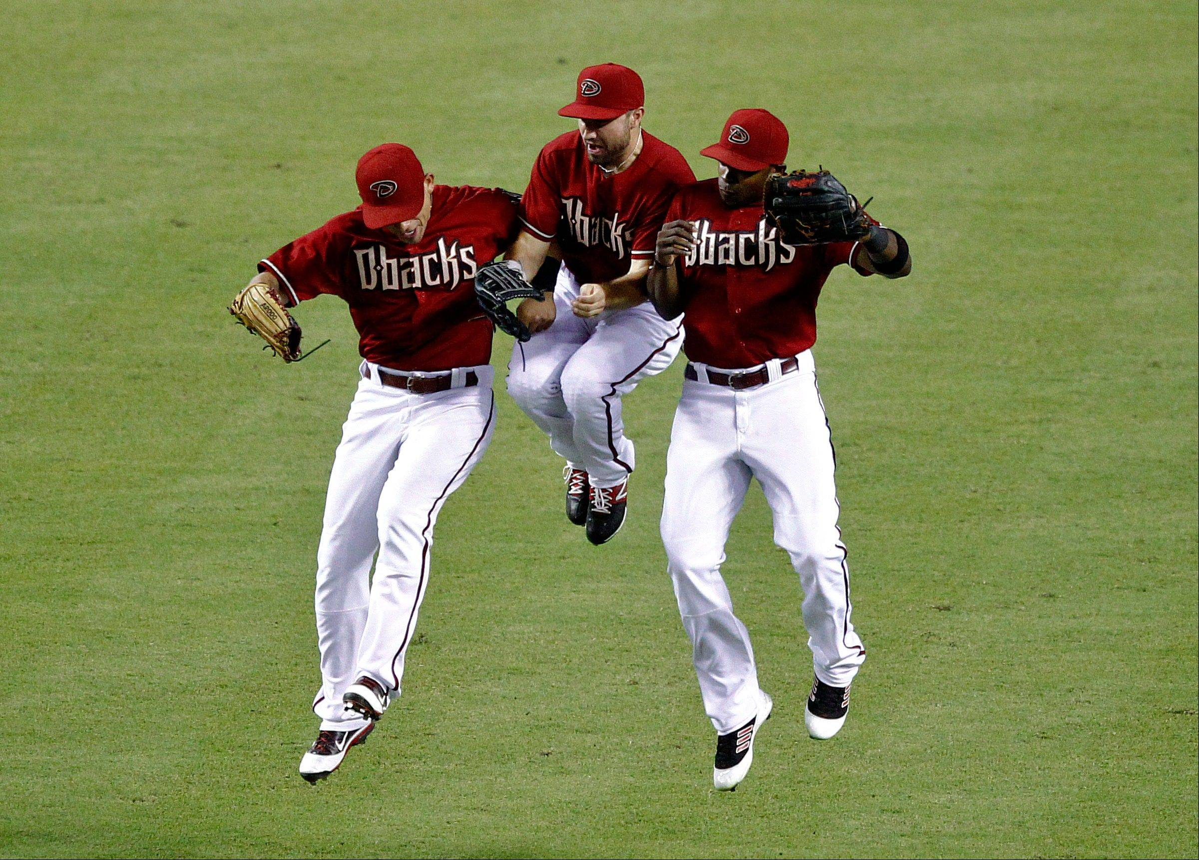 The Diamondbacks' Gerardo Parra, left, Adam Eaton, center, and Justin Upton celebrate their win over the Los Angeles Dodgers on Wednesday in Phoenix.