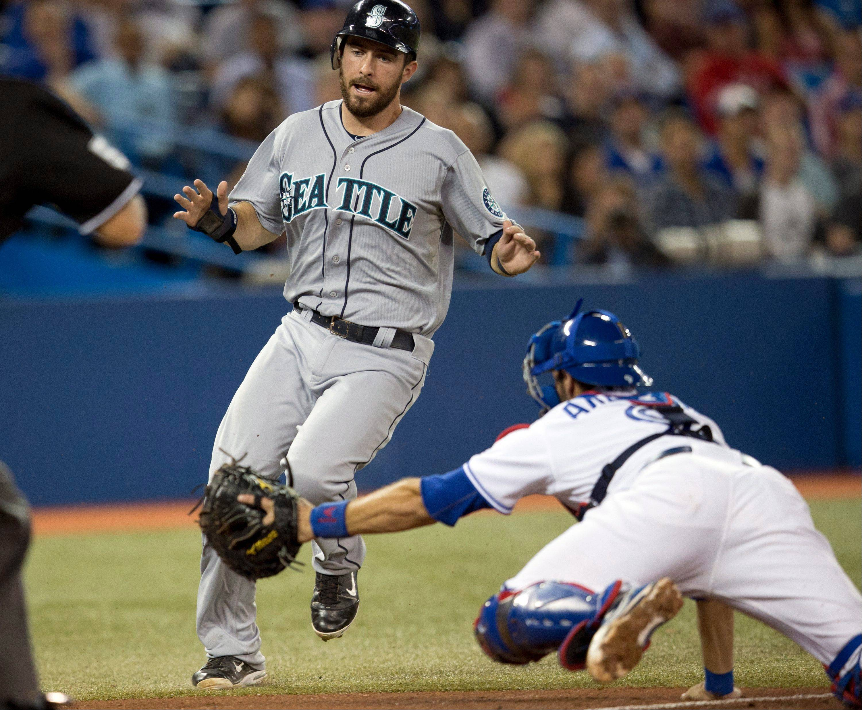 Seattle's Dustin Ackley dodges the tag of Blue Jays catcher J.P. Arencibia to score during the fourth inning Wednesday in Toronto.