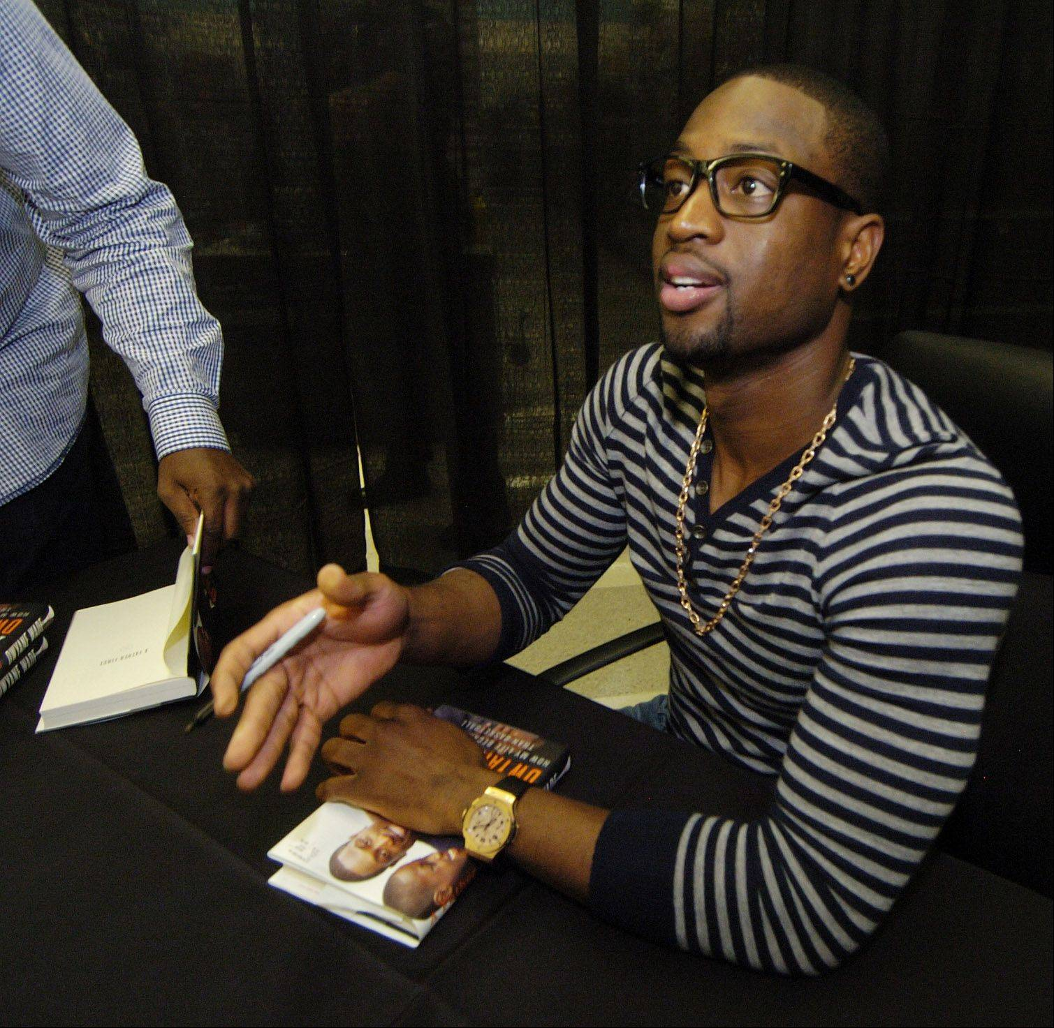 "Miami Heat star Dwyane Wade signs copies of his book, ""A Father First: How My Life Became Bigger Than Basketball,"" at the Rolling Meadows Meijer store on Wednesday."
