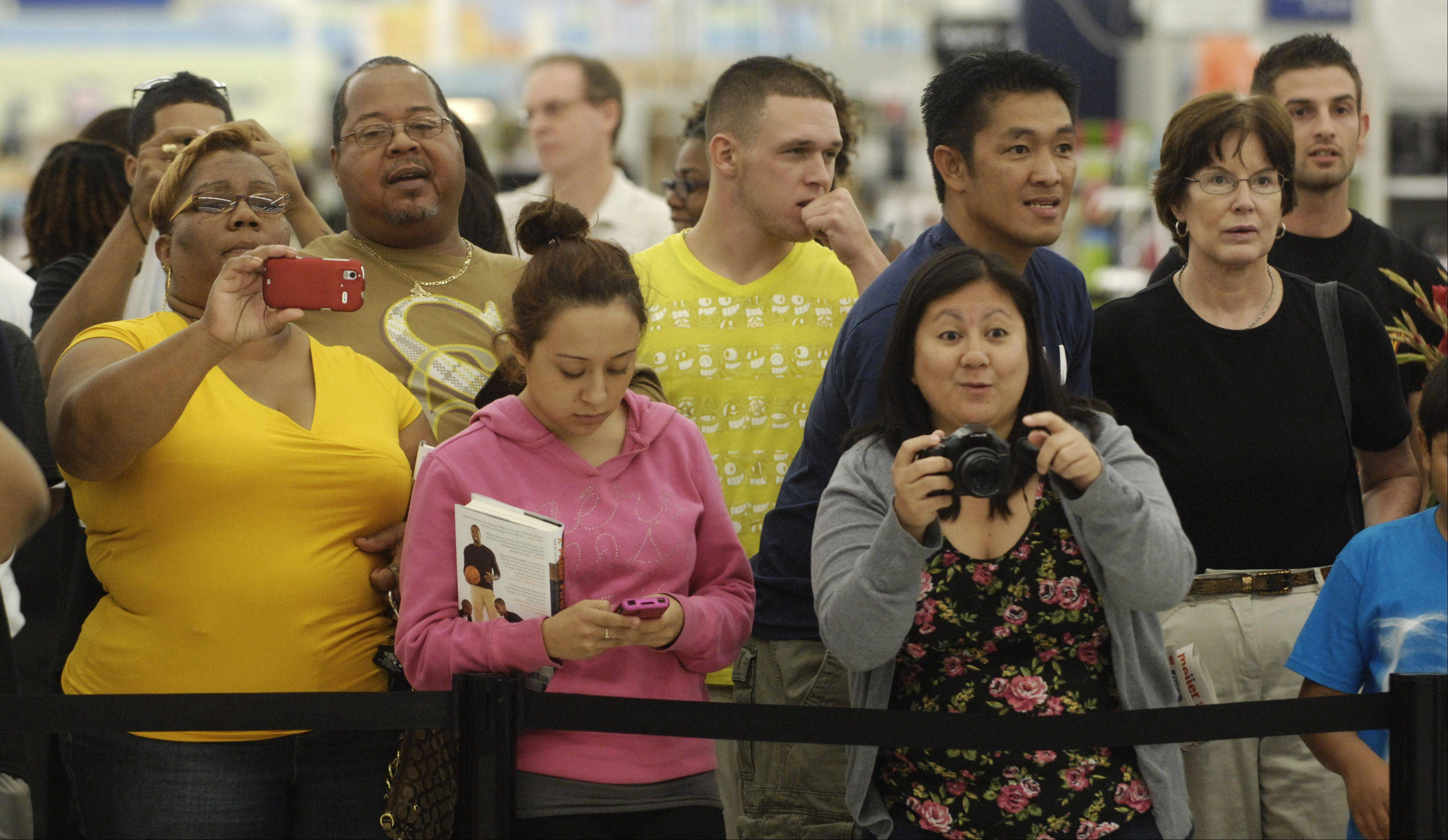 JOE LEWNARD/jlewnard@dailyherald.comFans take photos of Miami Heat star Dwyane Wade at the Rolling Meadows Meijer store Wednesday.