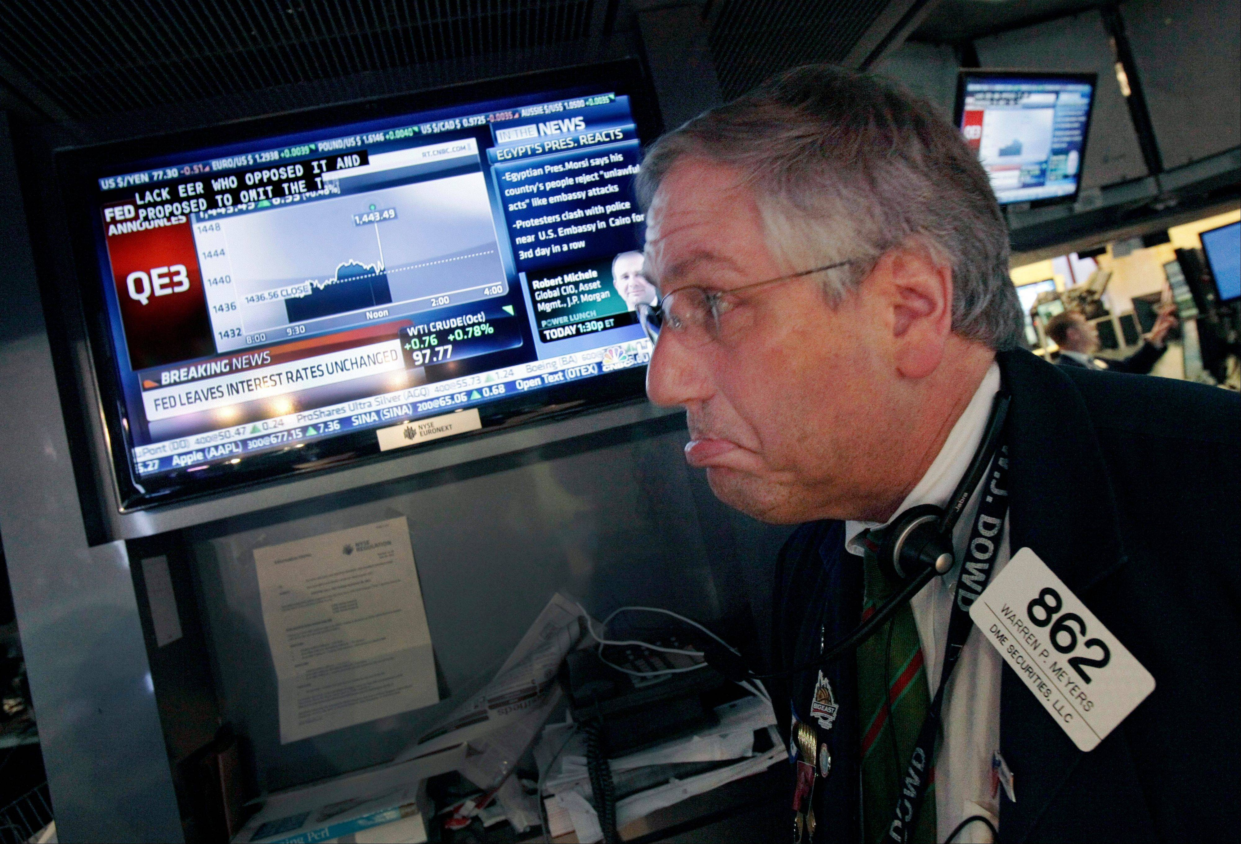 Trader Warren Meyers reacts to the announcement of the Federal Reserve as he watches a television screen Thursday on the floor of the New York Stock Exchange.