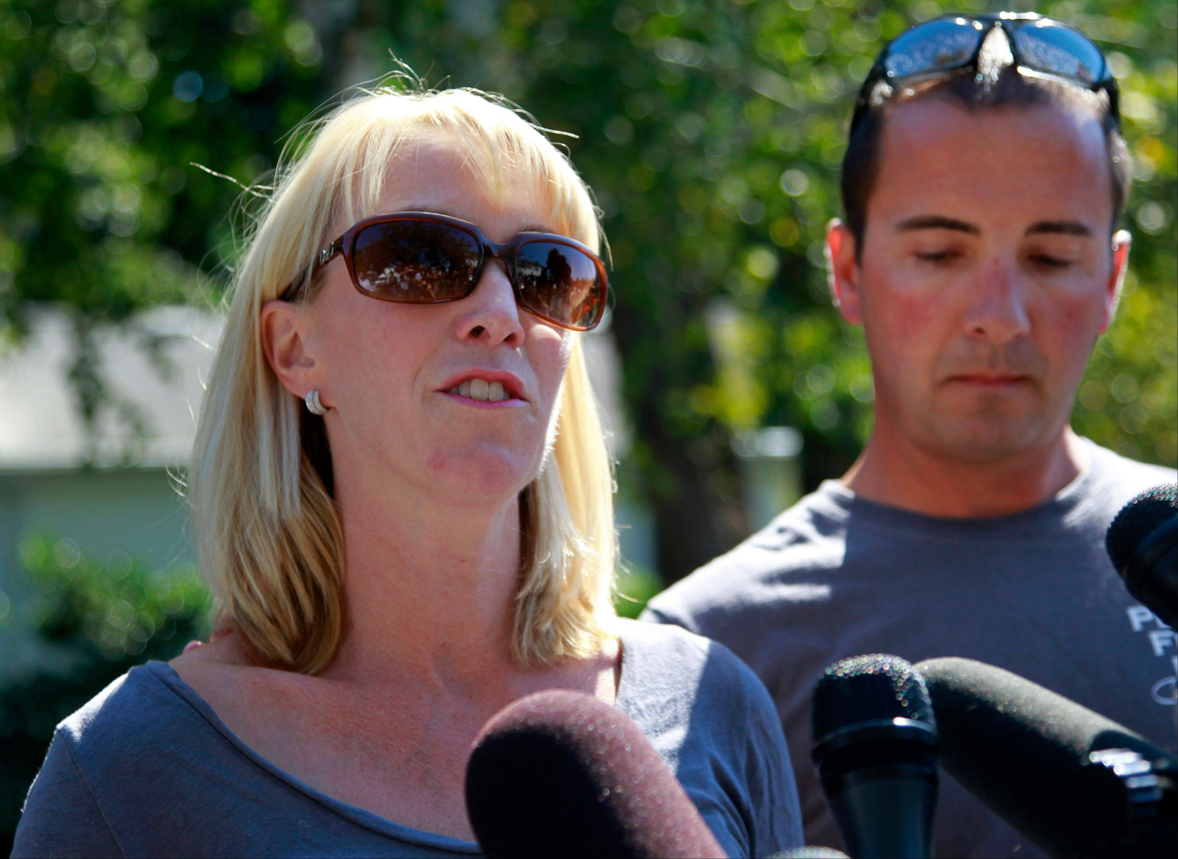 Kate Quigley, who says her brother Glen Doherty was among the Americans killed in an attack on the U.S. Consulate in Libya, faces reporters Thursday with her husband Mark Quigley, right.
