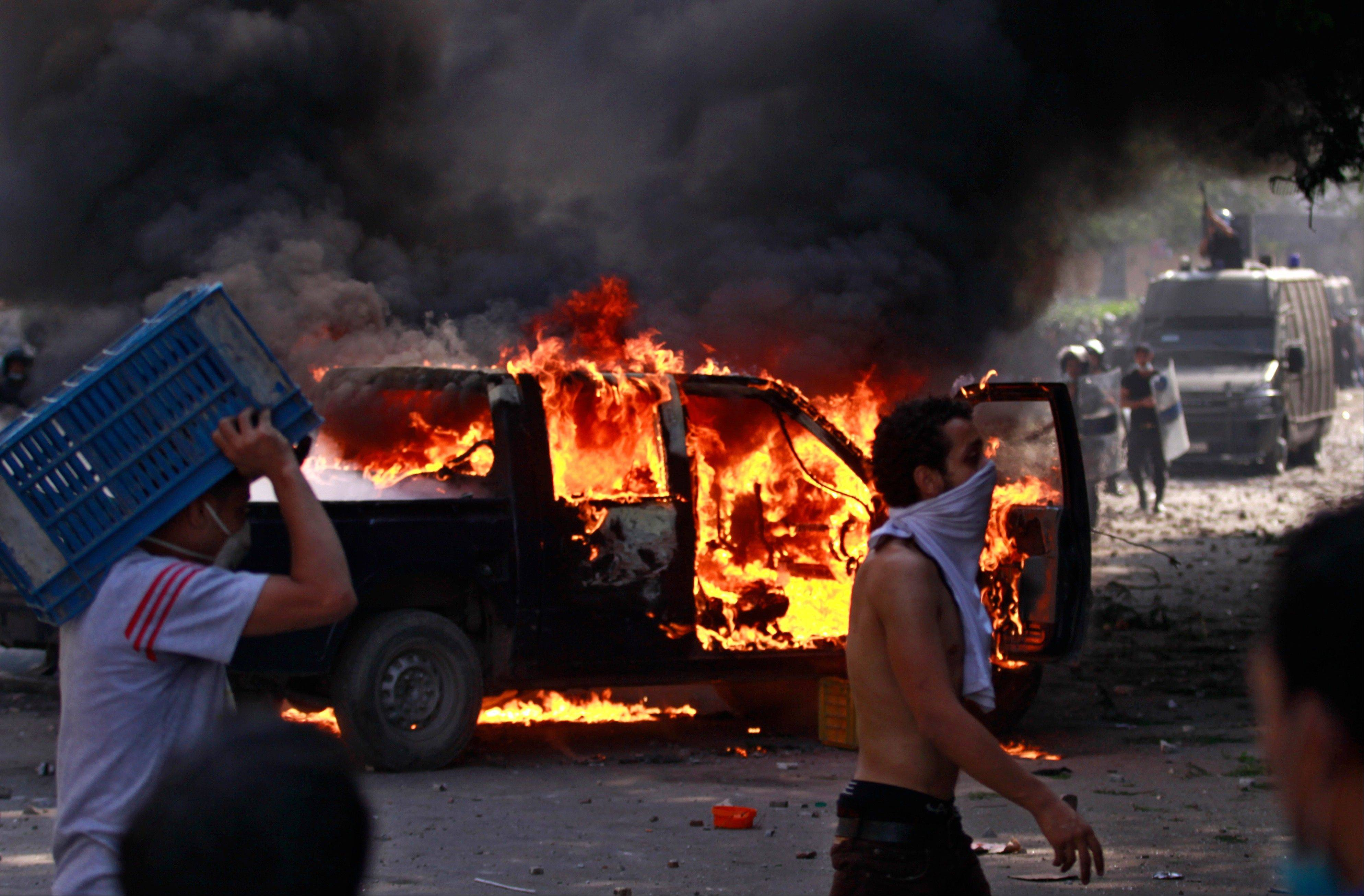 Egyptian protesters throw stones Thursday next to a burning police car during clashes near the U.S. embassy in Cairo.