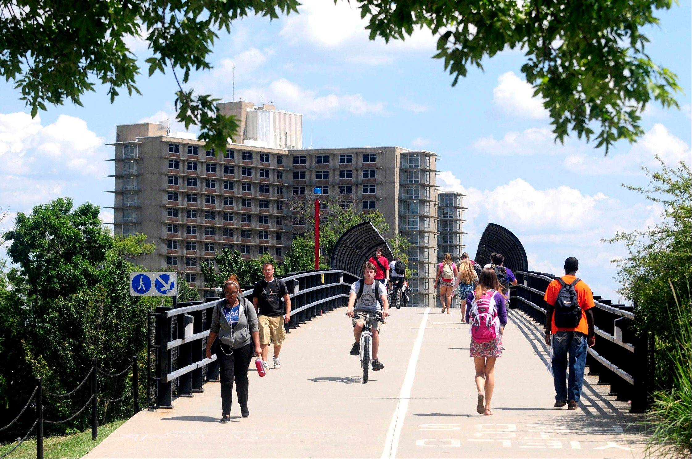 Students walk across a bridge on the first day of classes at Southern Illinois University in Carbondale on Aug. 20. Enrollment at many of Illinois� public universities is down this fall.