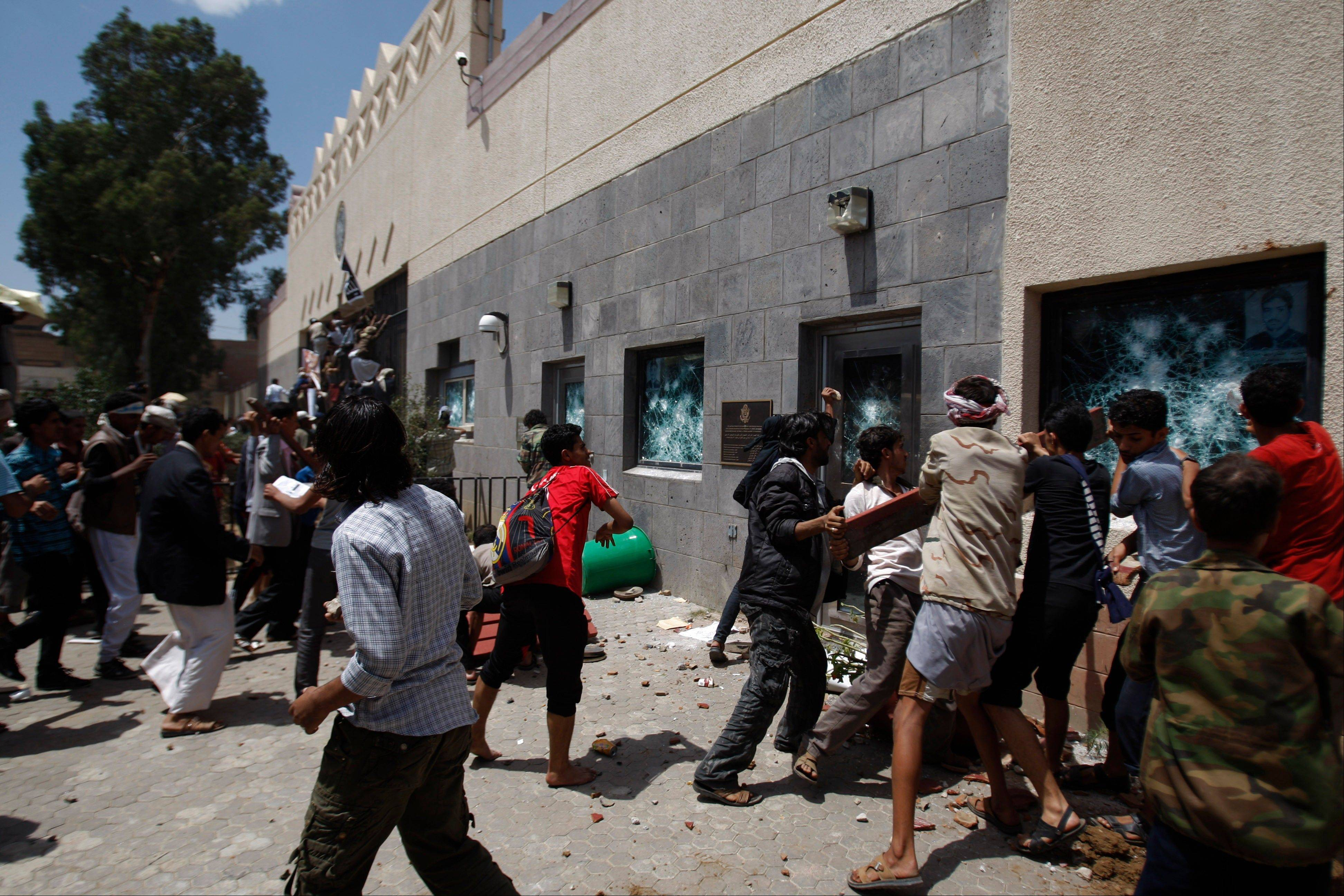 "Yemeni protestors break windows of the U.S. Embassy during a protest about a film ridiculing Islam's Prophet Muhammad, in Sanaa, Yemen, Thursday, Sept. 13, 2012. Dozens of protesters gather in front of the US Embassy in Sanaa to protest against the American film ""The Innocence of Muslims"" deemed blasphemous and Islamophobic."