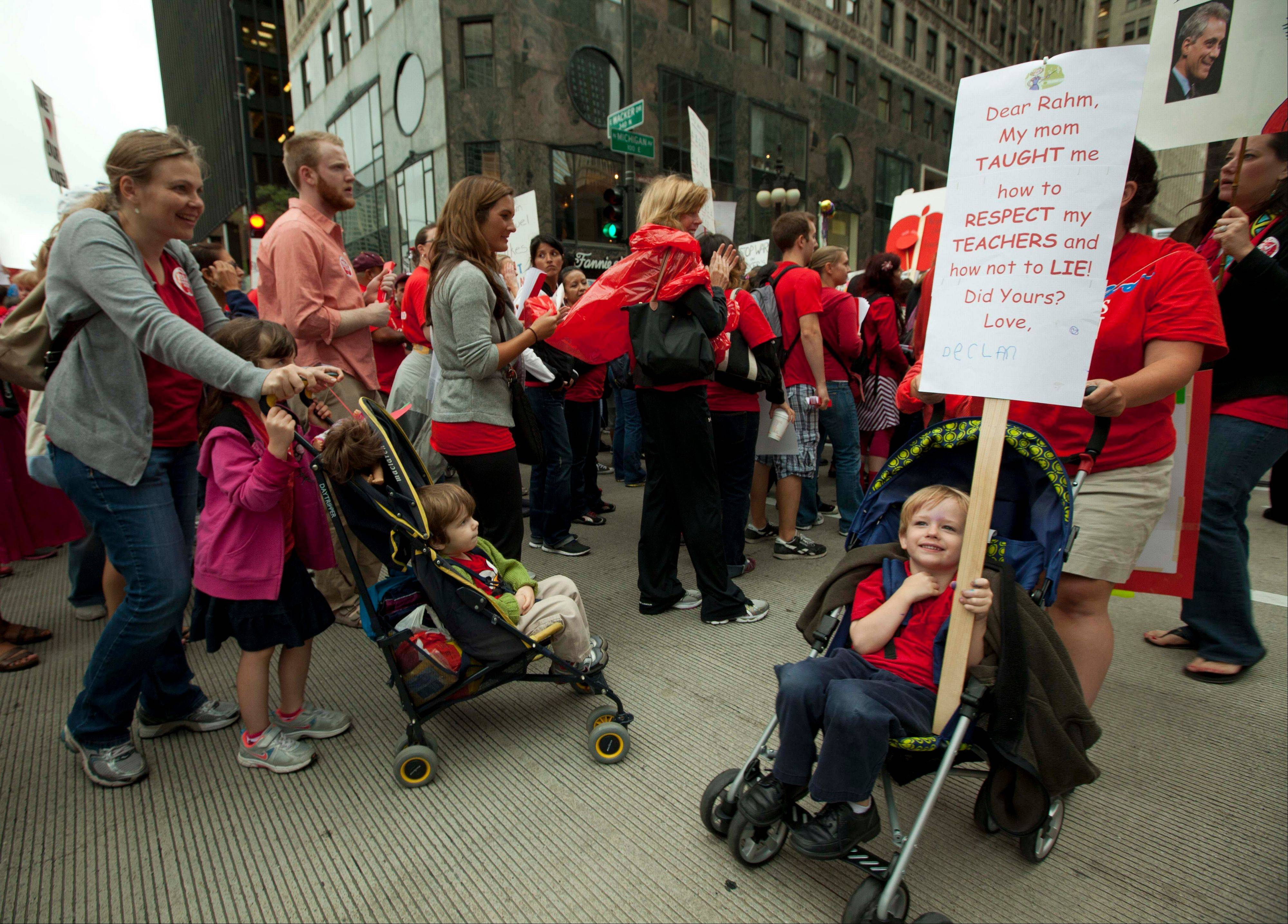 Children in strollers join thousands of public school teachers rallying outside the Hyatt Regency Hotel on Thursday. The teachers were protesting against Penny Pritzker, whom they accuse of benefiting from her position on the boards of both the Chicago Board of Education and Hyatt Hotels.
